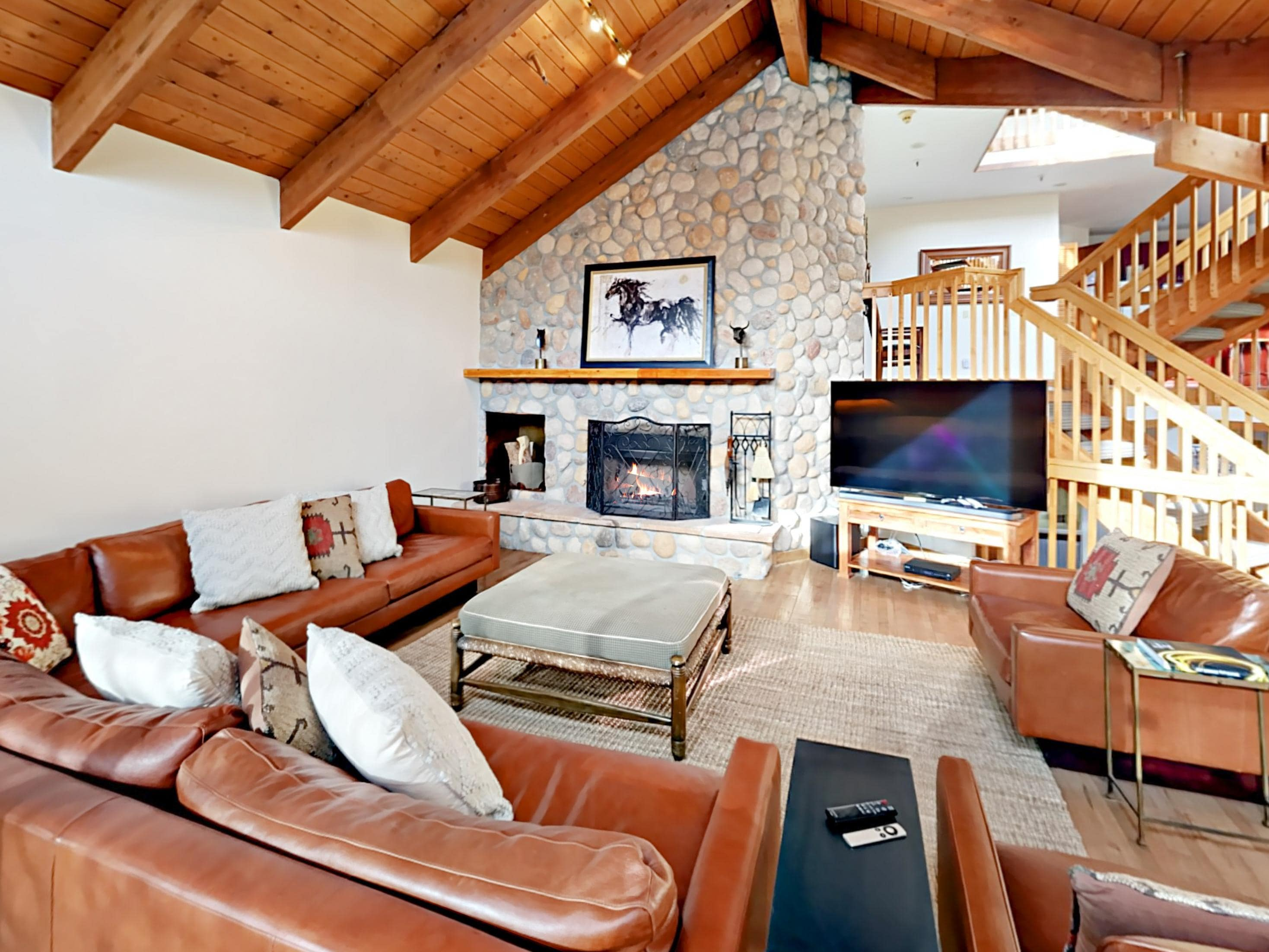 Welcome to your townhouse in Park City! A grand living room boasts vaulted wood ceilings and a stone wall feature with a wood burning fireplace.