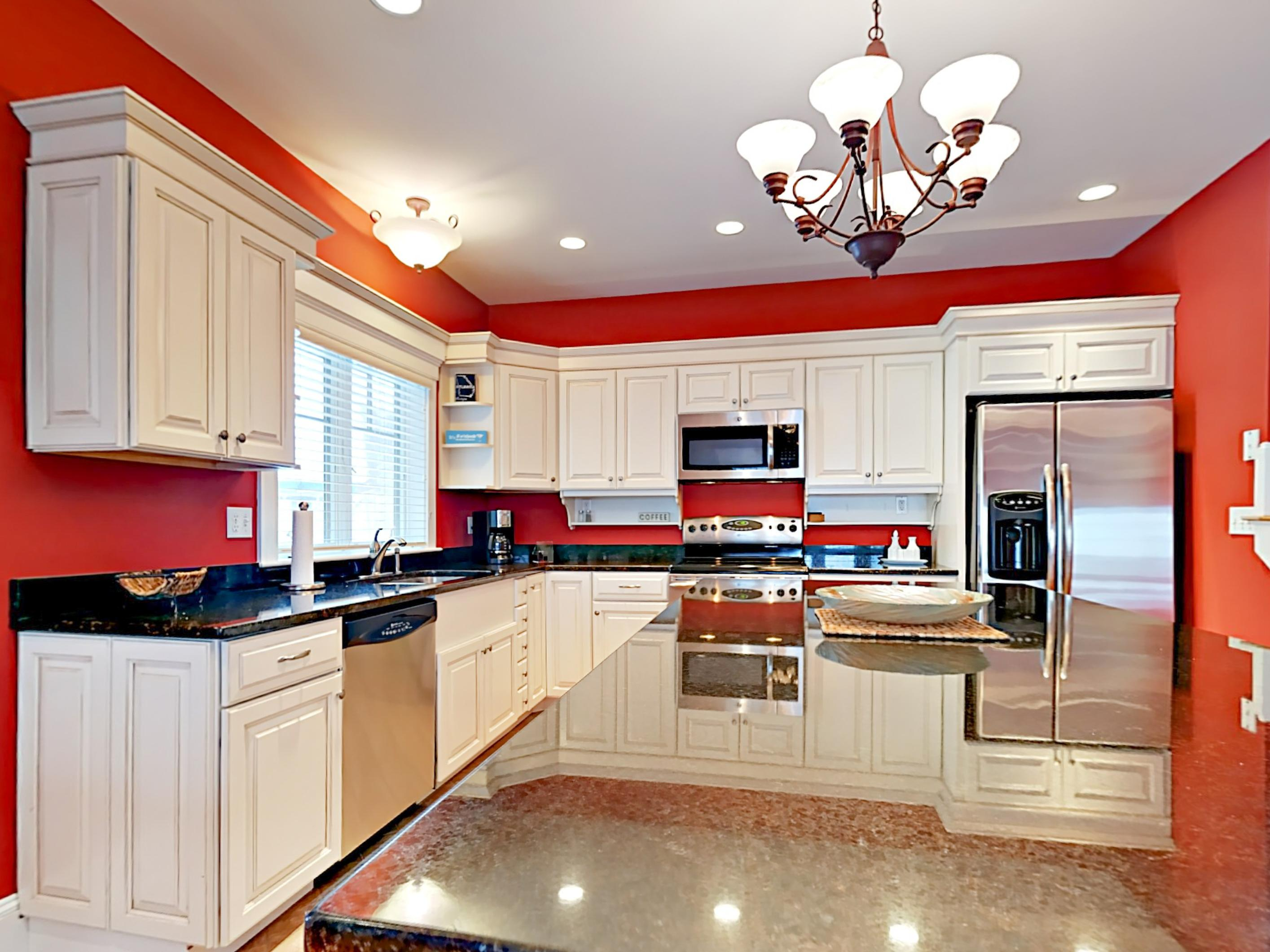 Marble countertops and stainless-steel appliances shine in the well-equipped kitchen.