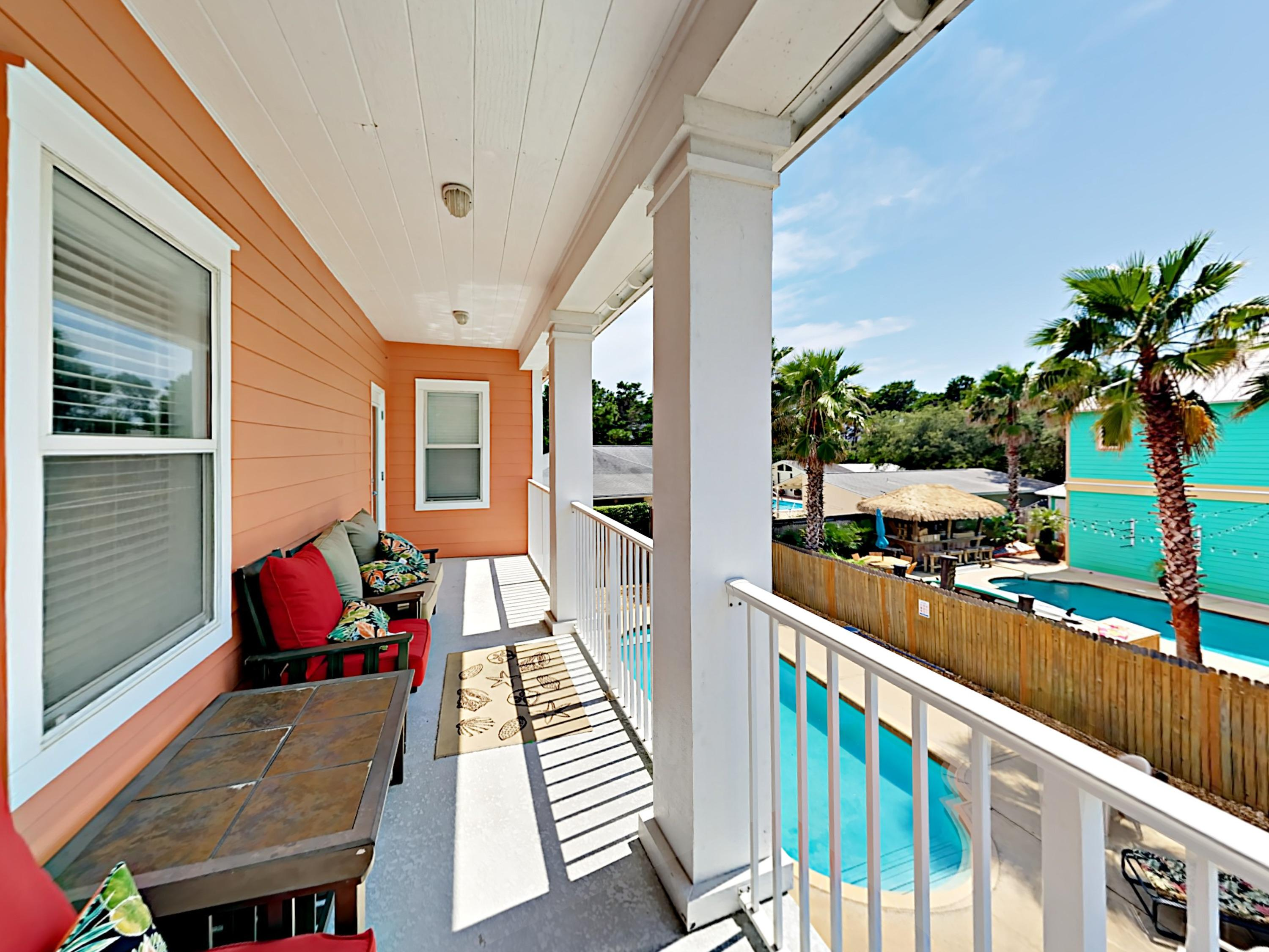Relax on the covered, wraparound balcony overlooking the backyard and pool.