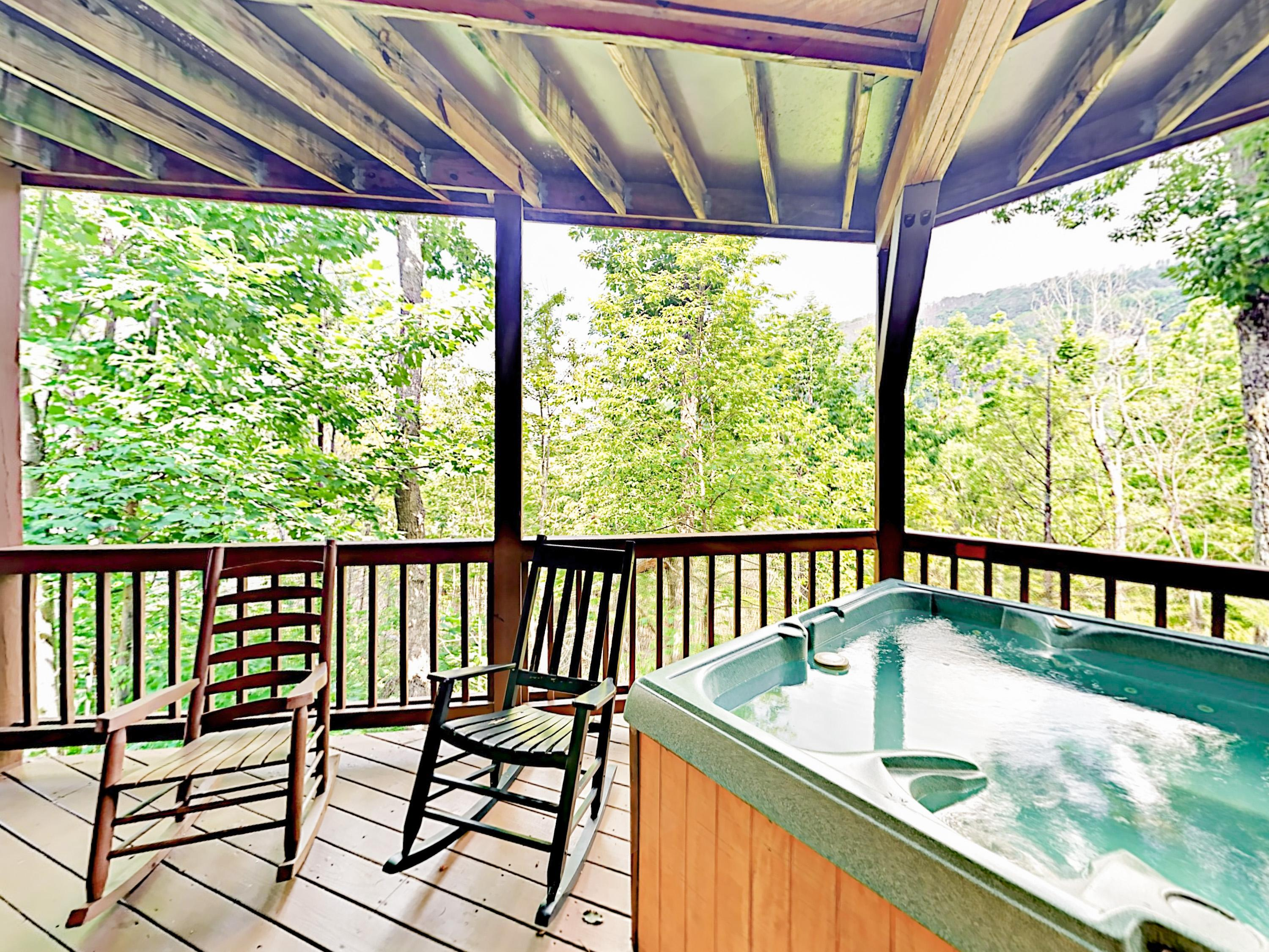 Soak in the private hot tub with treetop mountain views.