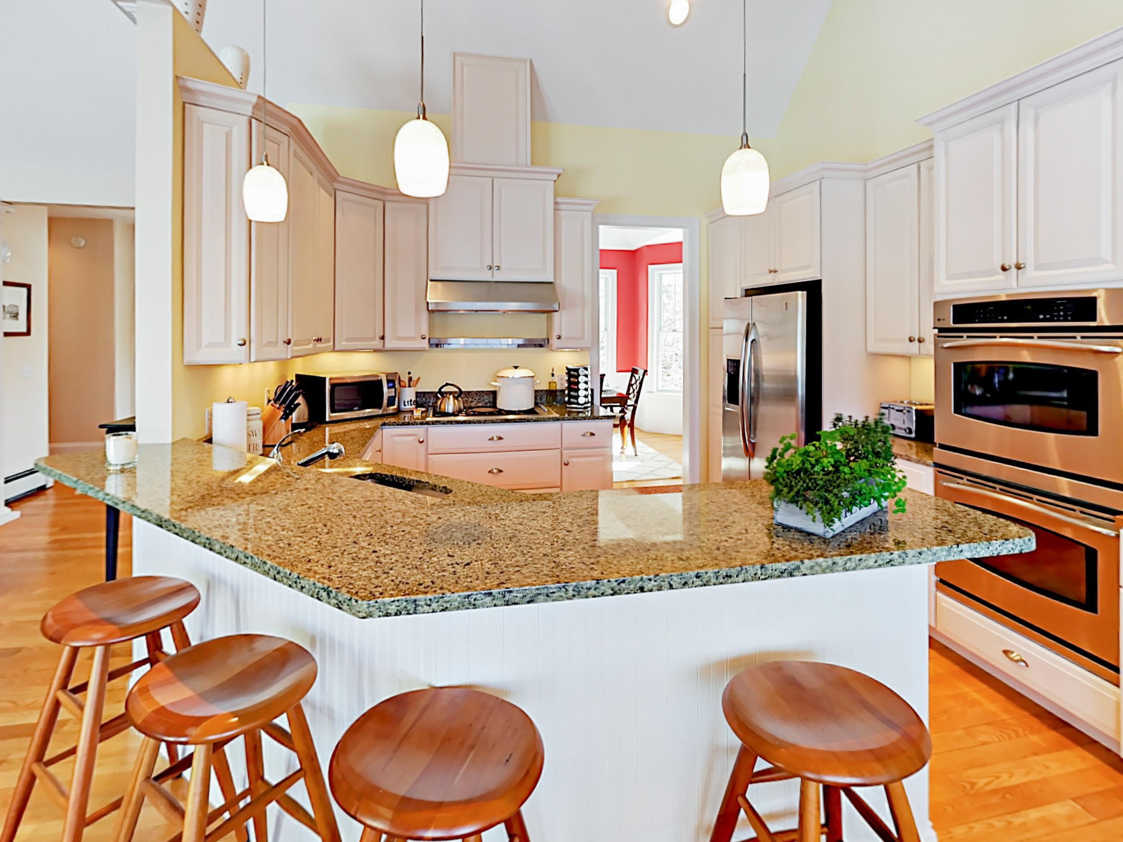 Granite-lined kitchen with stainless steel appliances and breakfast bar for 4.