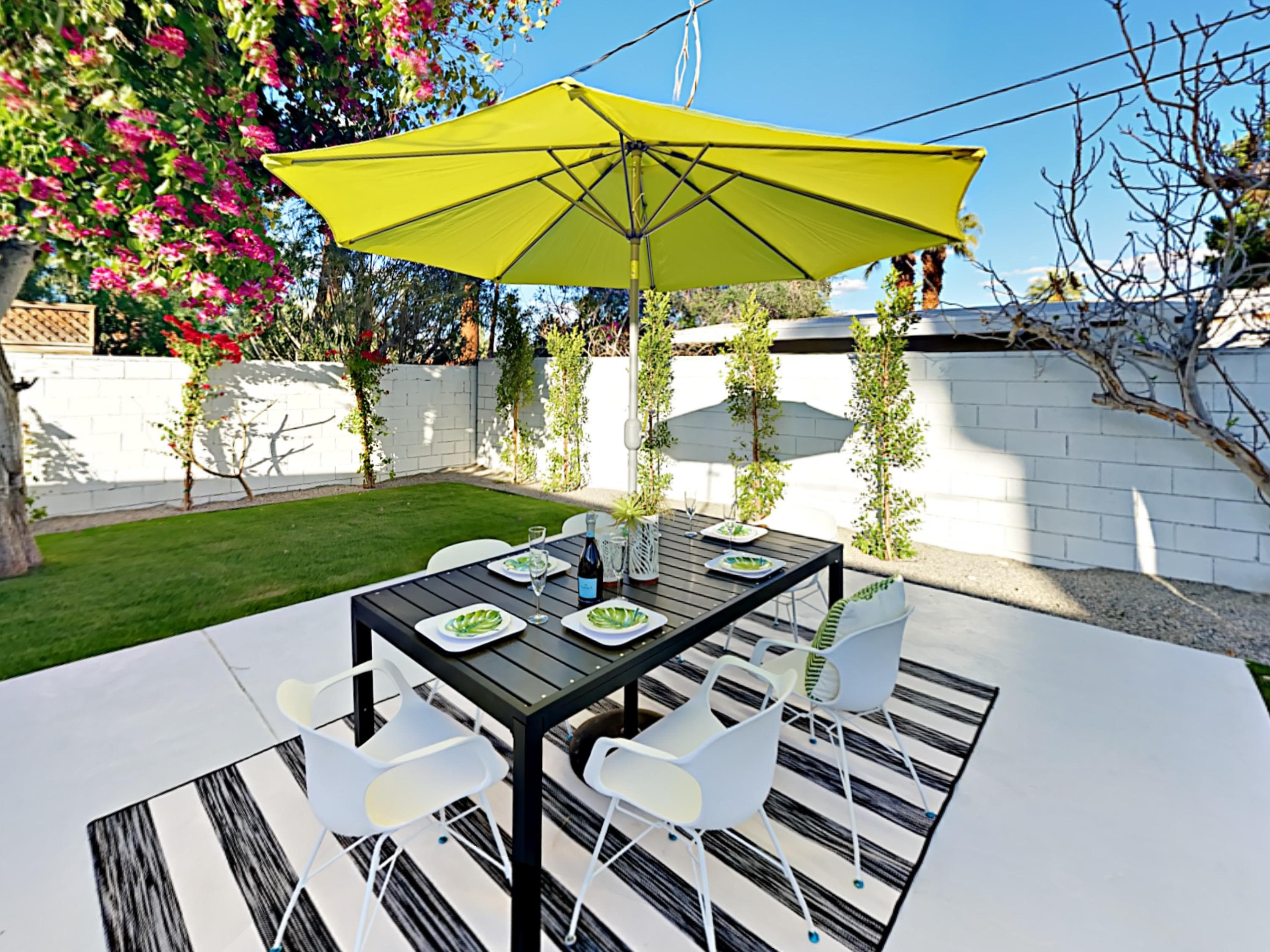Dine al fresco at the 6-person table under the shade of the large umbrella.