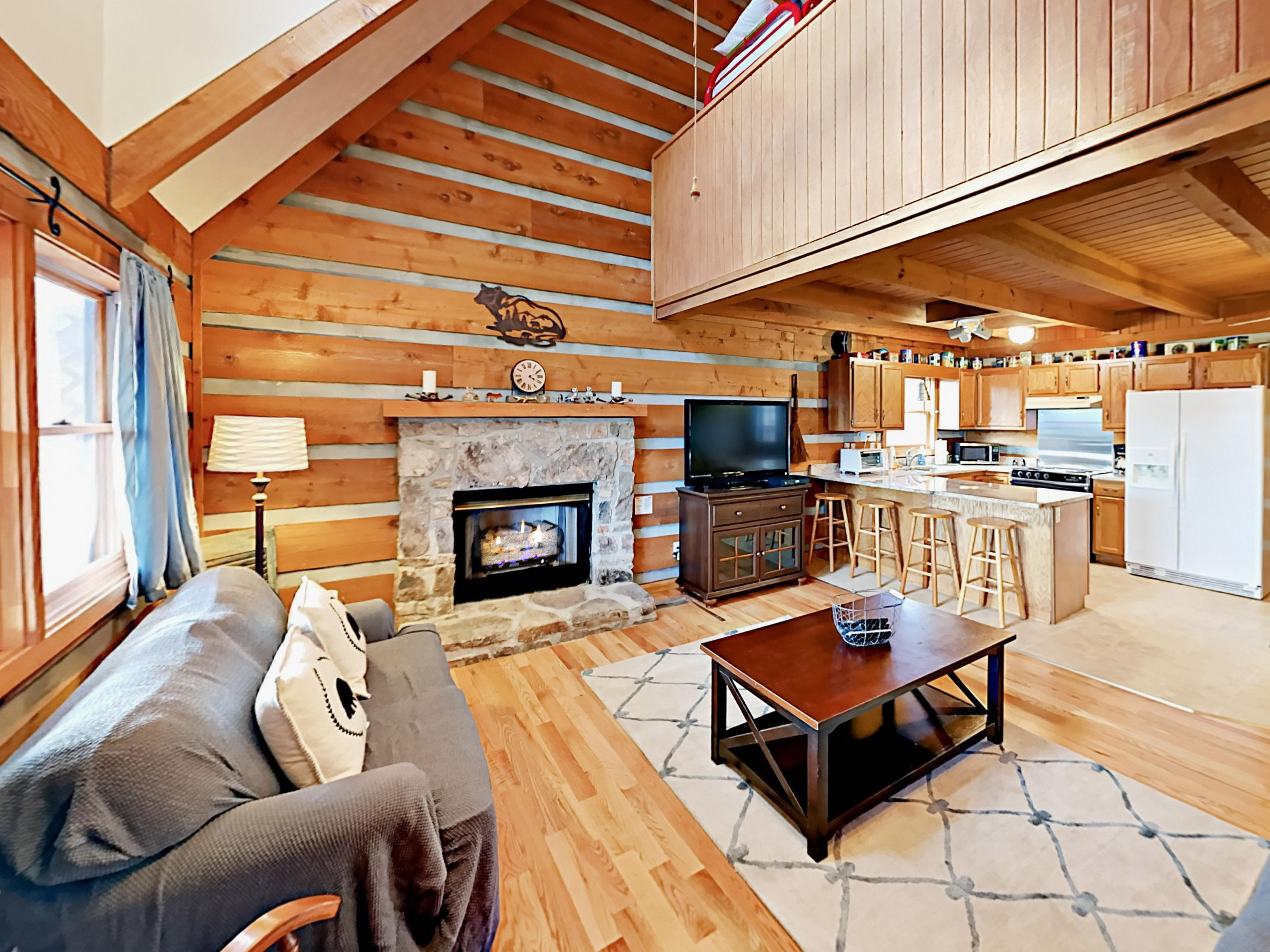Oversize living area with soaring ceilings, gas fireplace, and warm wood tones.