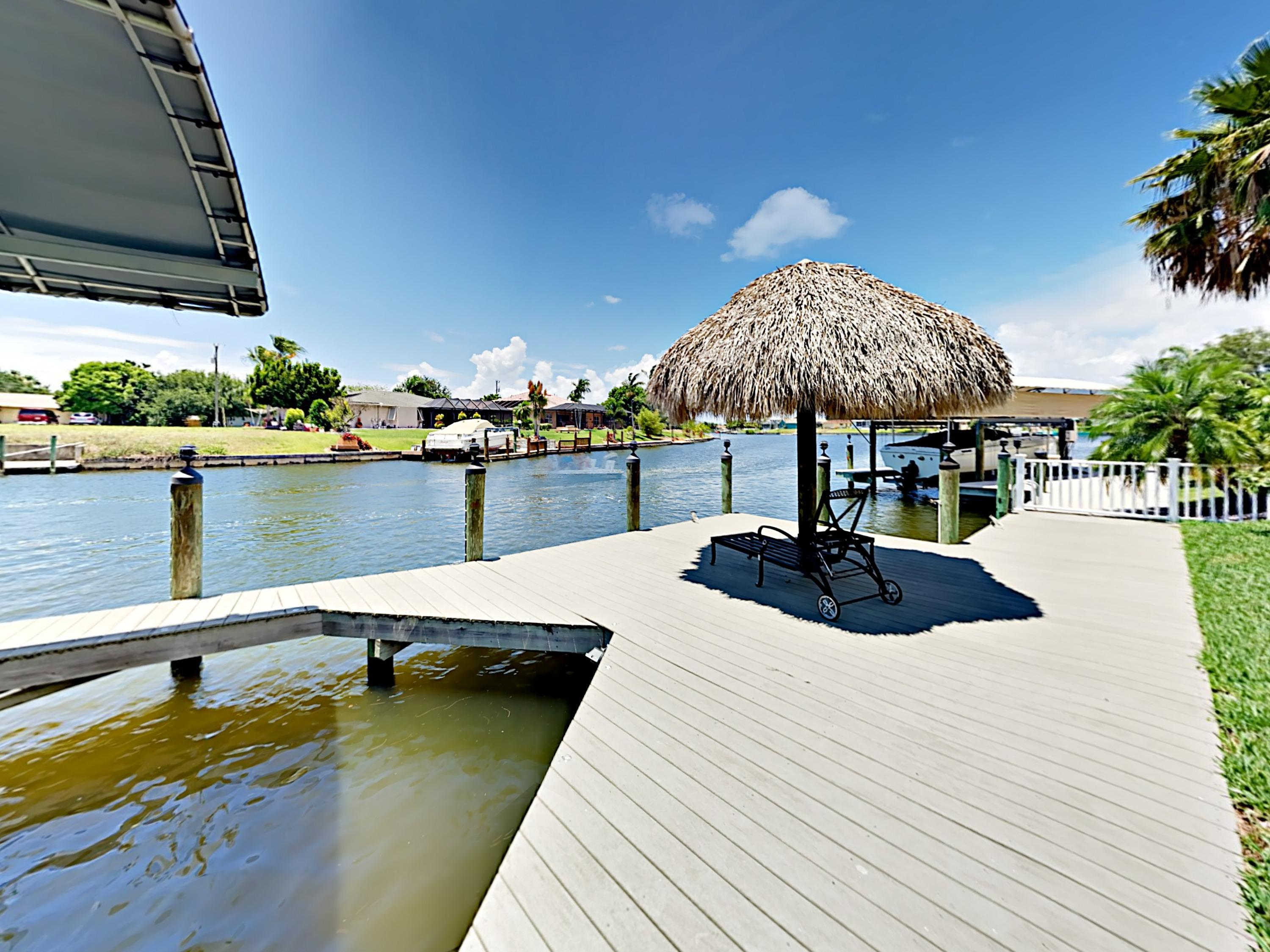 The house offers access to a canal-side boat dock with tiki hut.