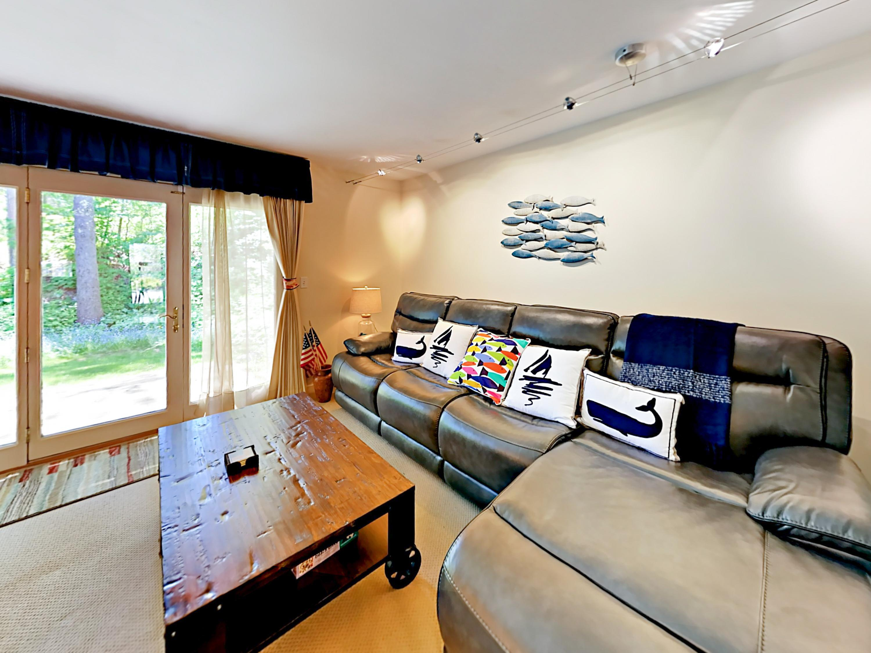 Welcome to Boothbay Harbor! Large black sofa offers comfy seating for 4 in the living area. Condo is professionally managed by TurnKey Vacation Rentals.