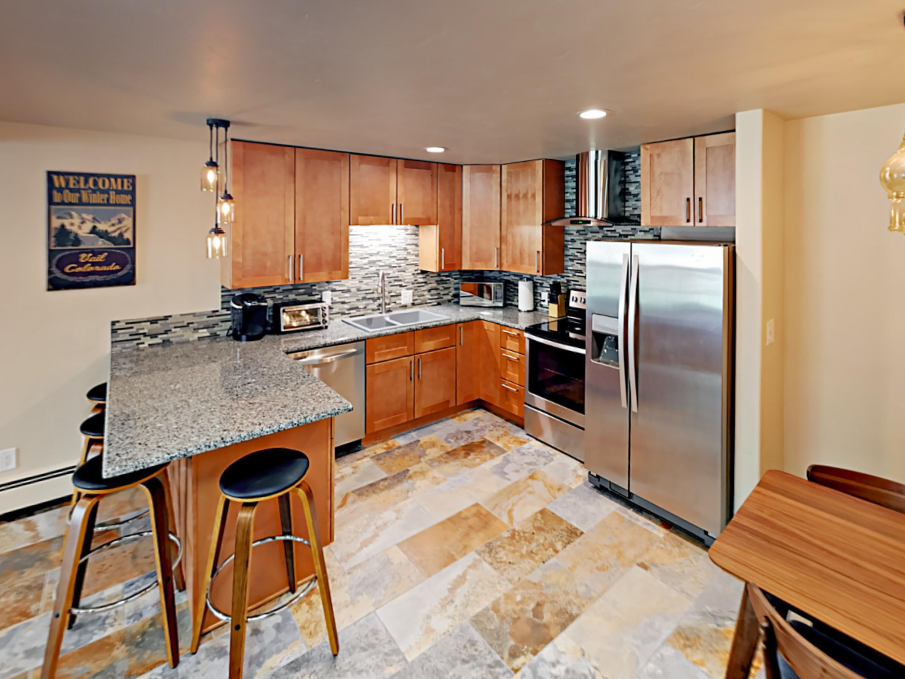 Fully equipped kitchen with breakfast bar for 4, a dual sink, and brand-new stainless steel appliances.