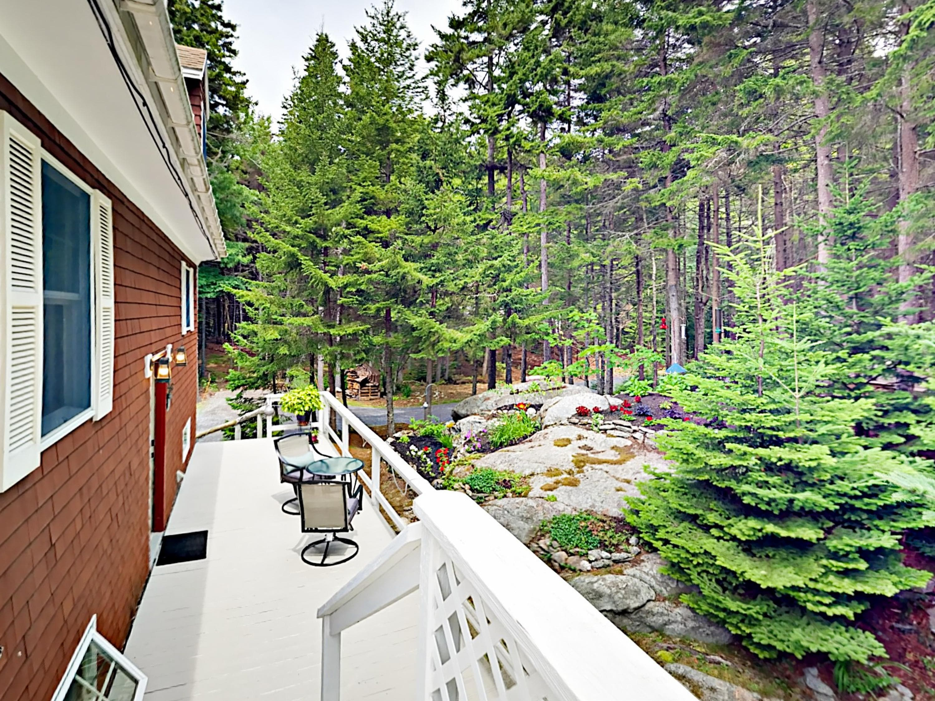 The side deck offers views of the garden and surrounding forest.