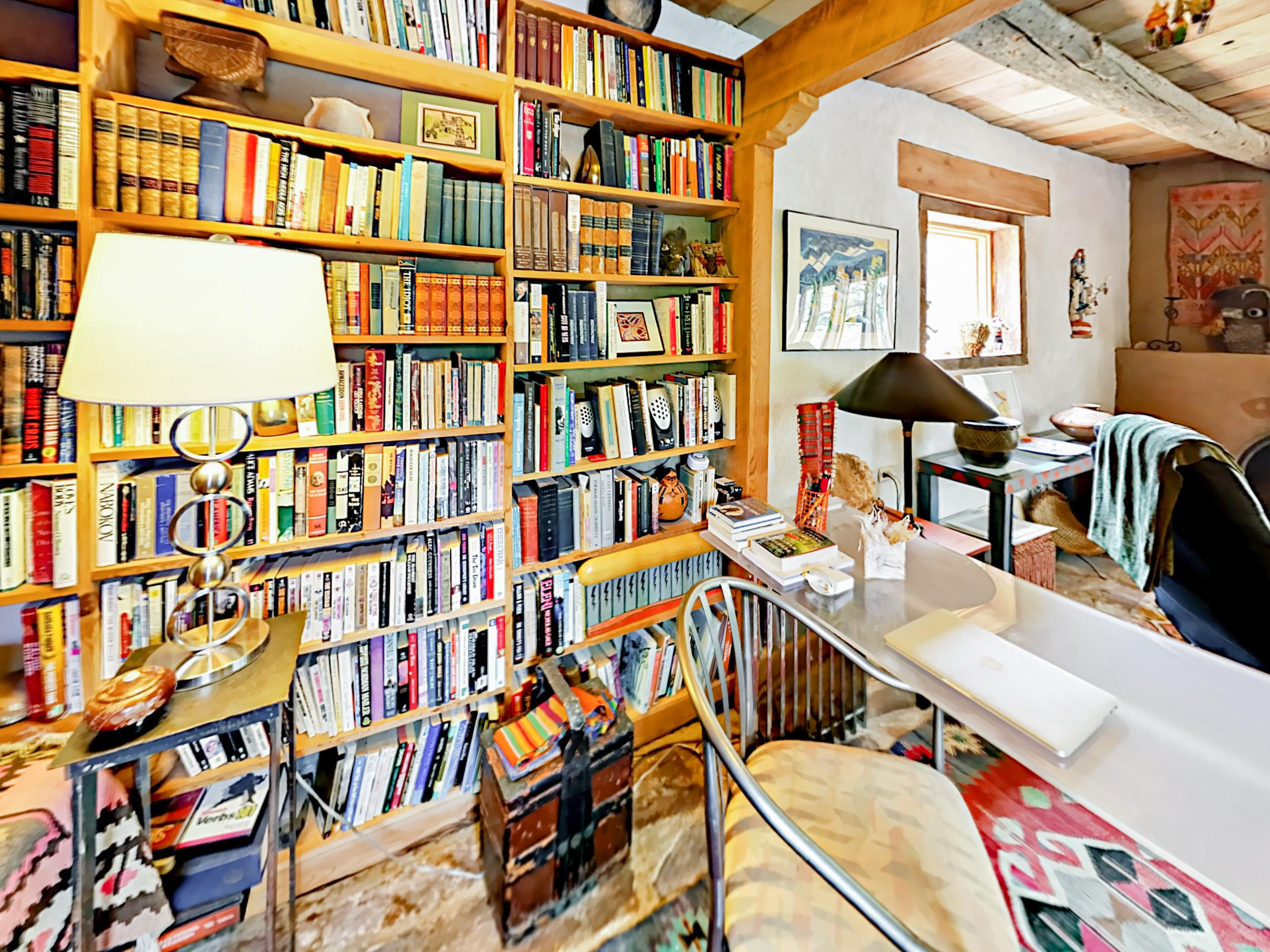 The master bedroom includes an office nook filled with books.