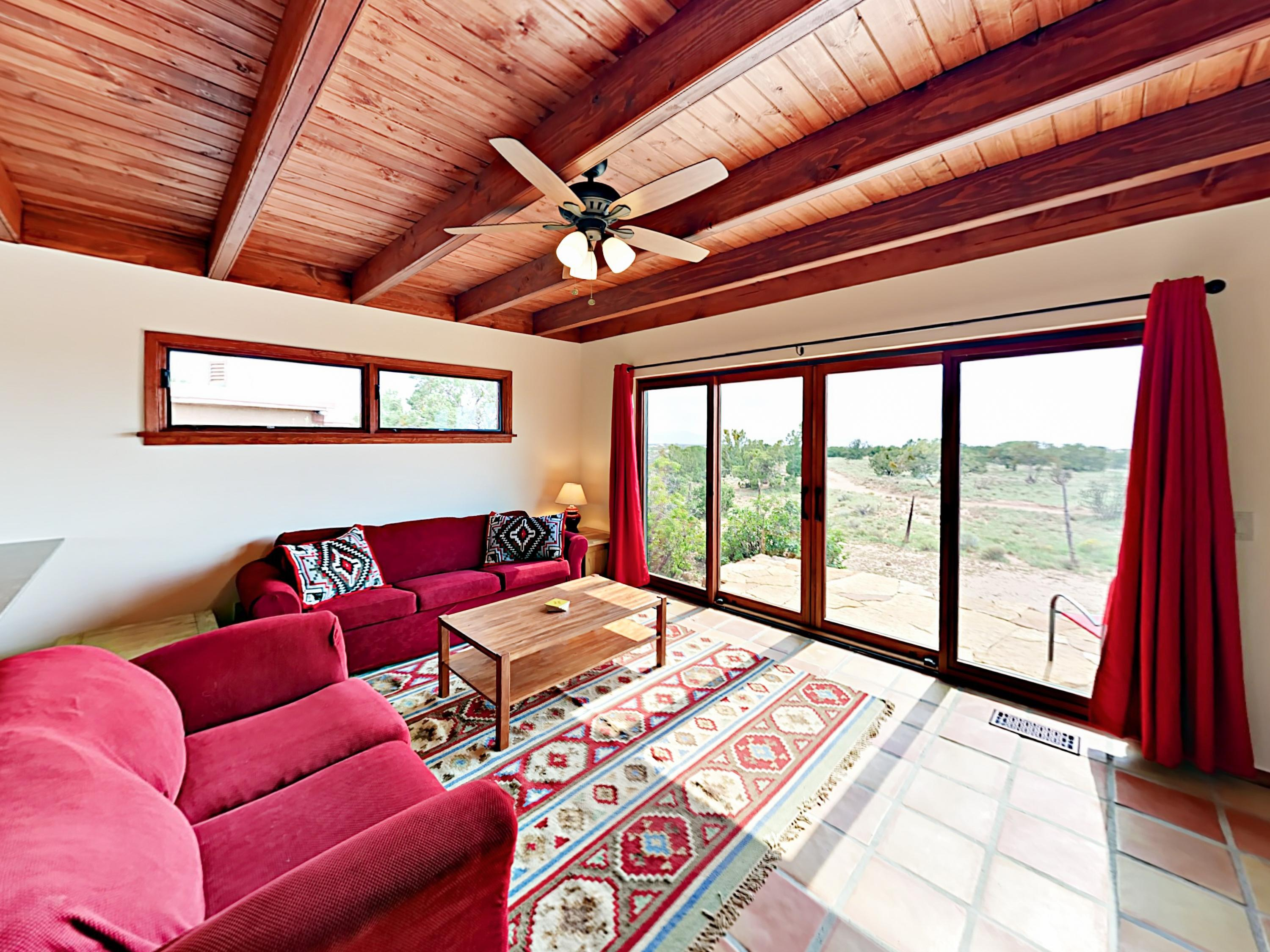 Beautiful Saltillo tiled floors, exposed-beam ceilings, and rich red hues give this Santa Fe home a distinct Southwestern feel.