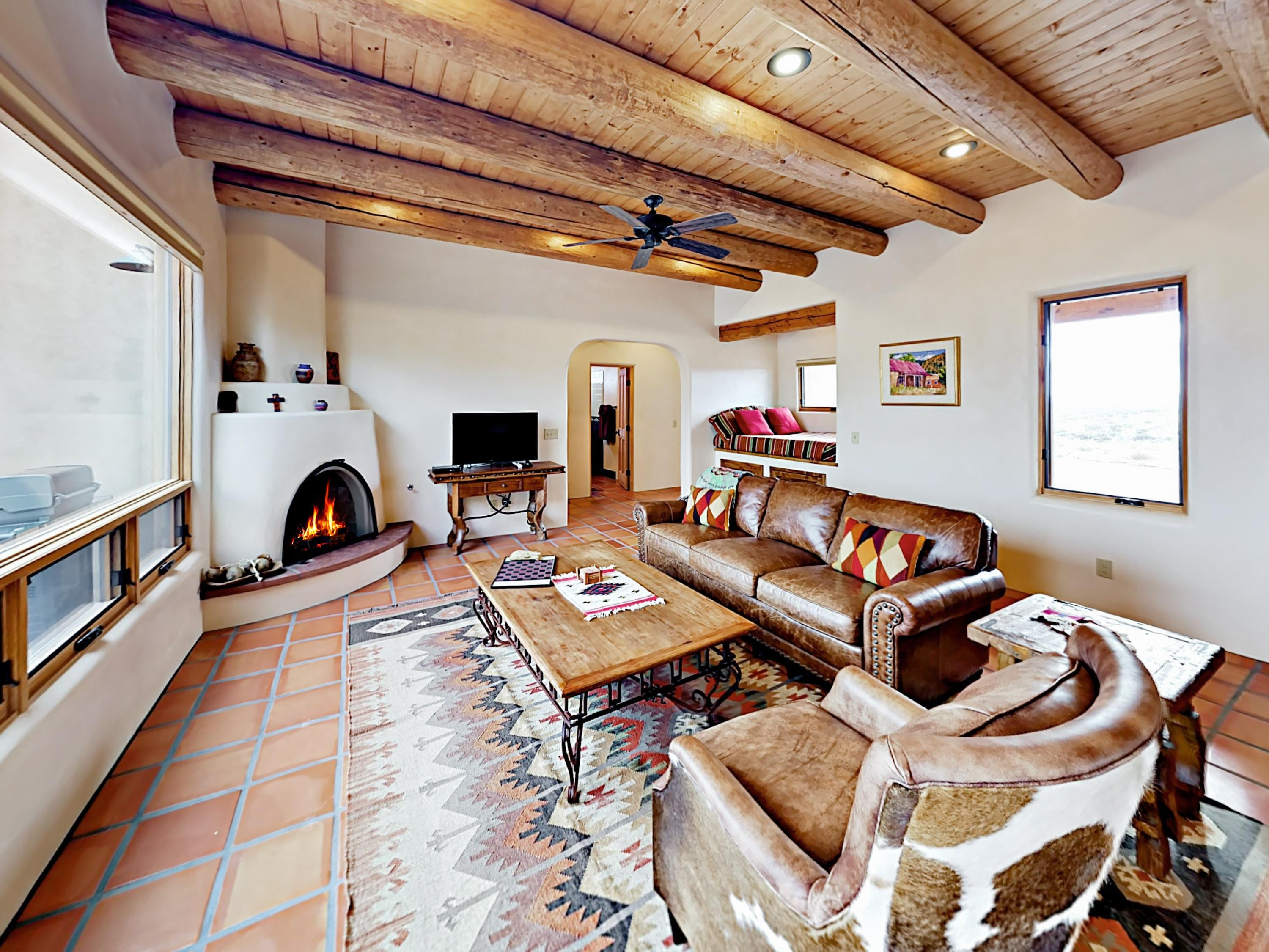 Open beam ceilings complement tile floors and adobe walls in the airy living room.