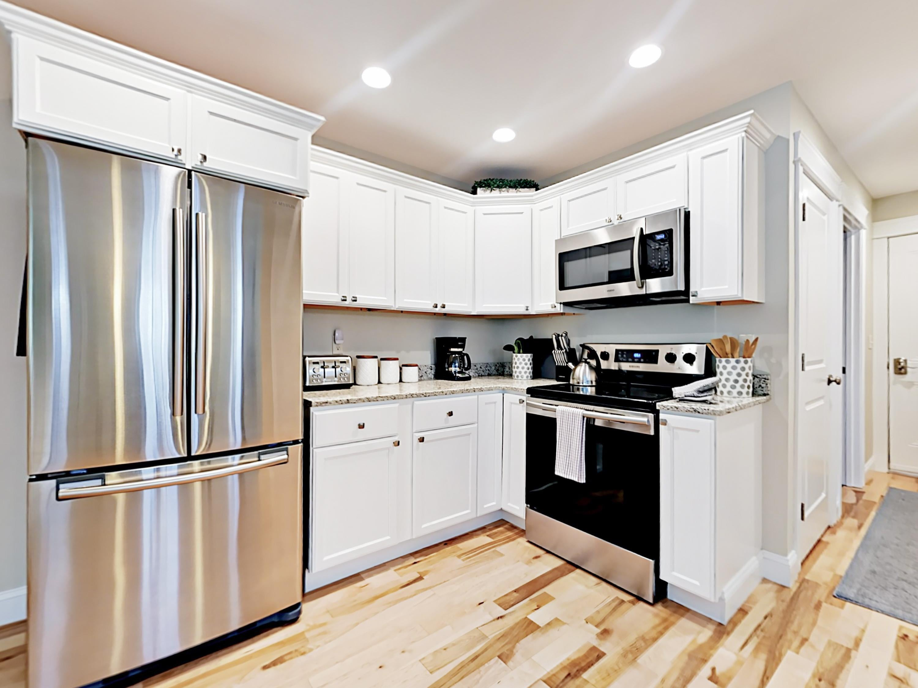 Stainless steel appliances and granite counters line the kitchen. TurnKey provides a starter supply of dish soap and paper towels.