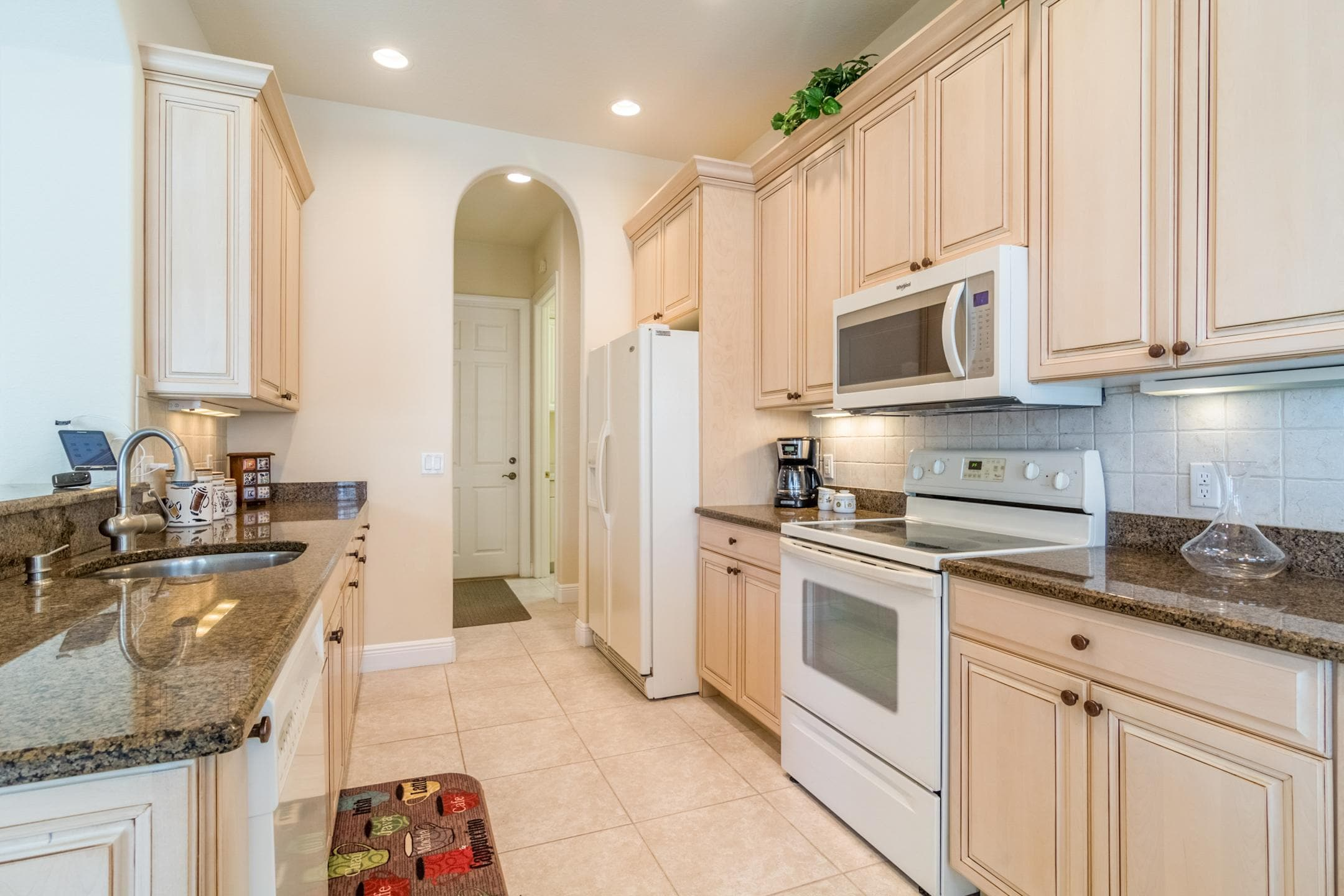 Arched doorways and sparkling granite countertops set an elegant tone in the gourmet kitchen.