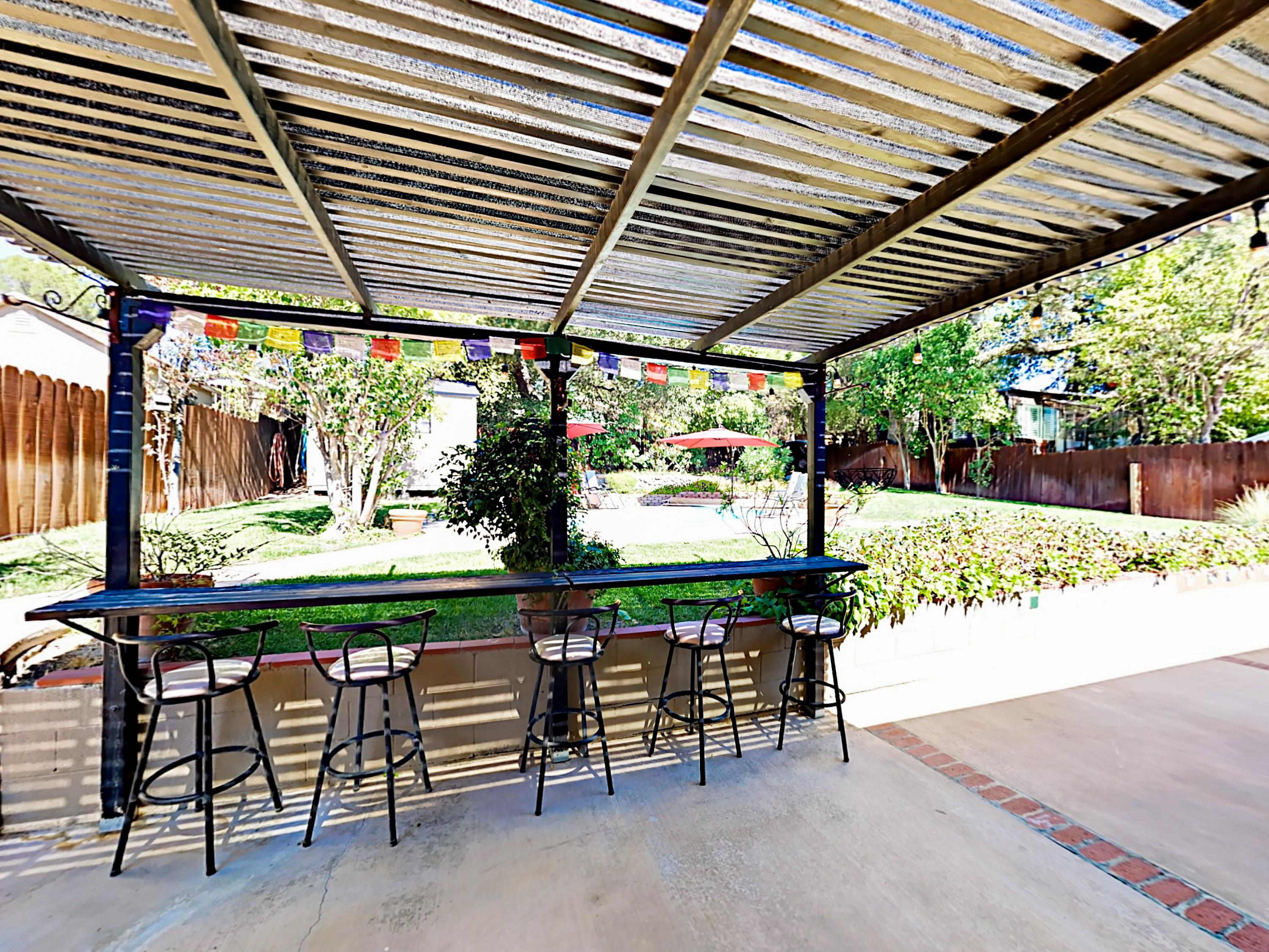 A covered bar area on the patio is the perfect place to enjoy a drink.