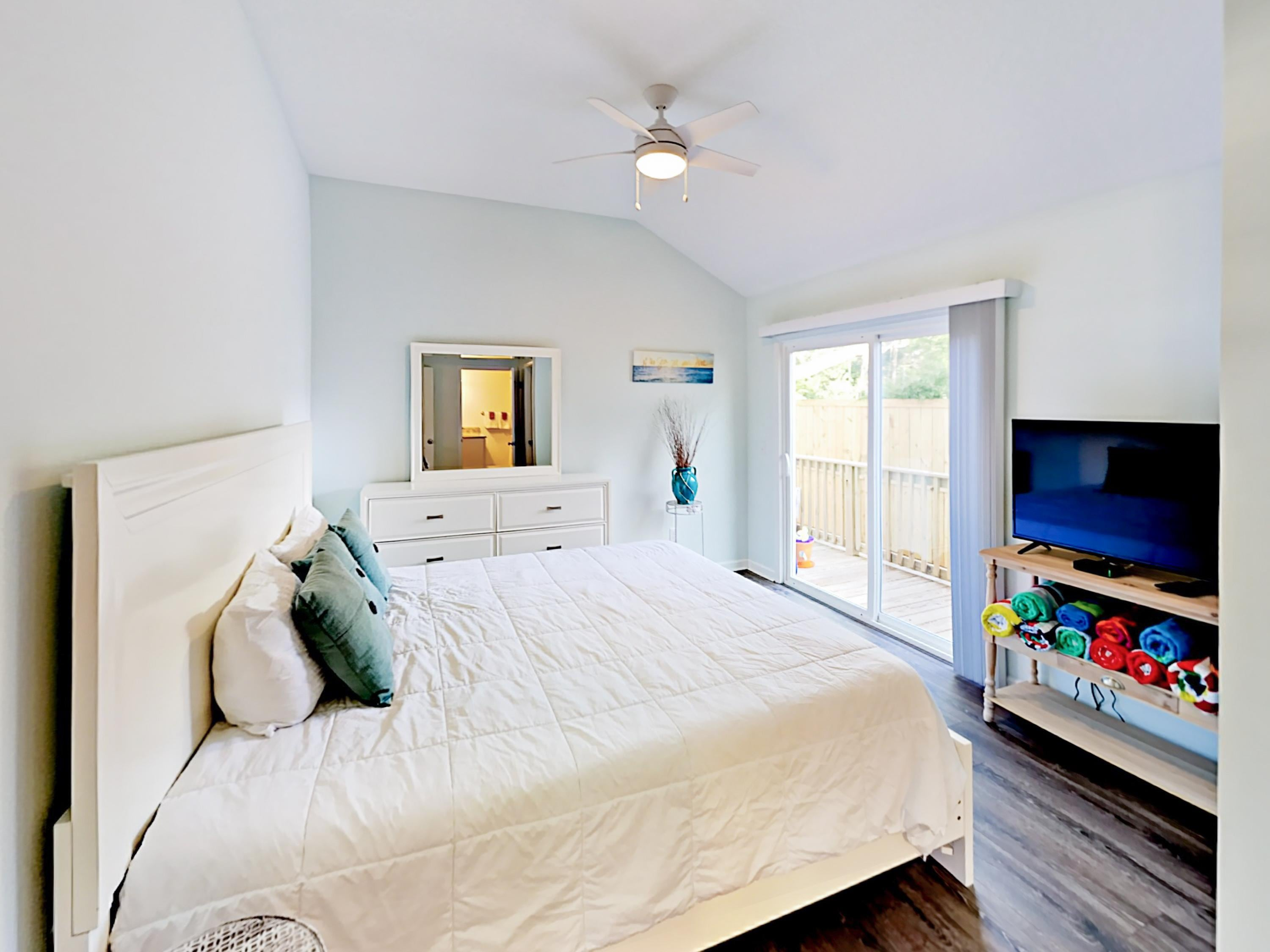 "The sunny master bedroom features a king-size bed and a 48"" TV."