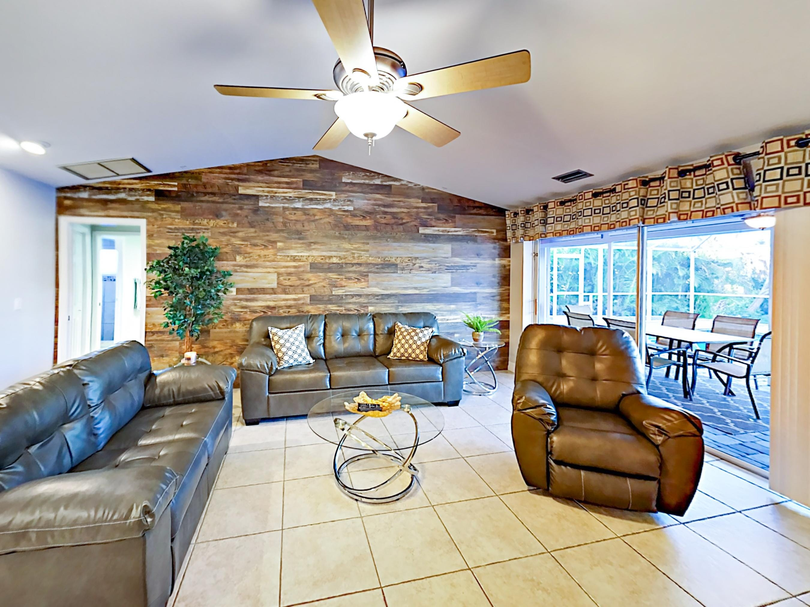 The living room features a wood accent wall and provides direct access to the patio.
