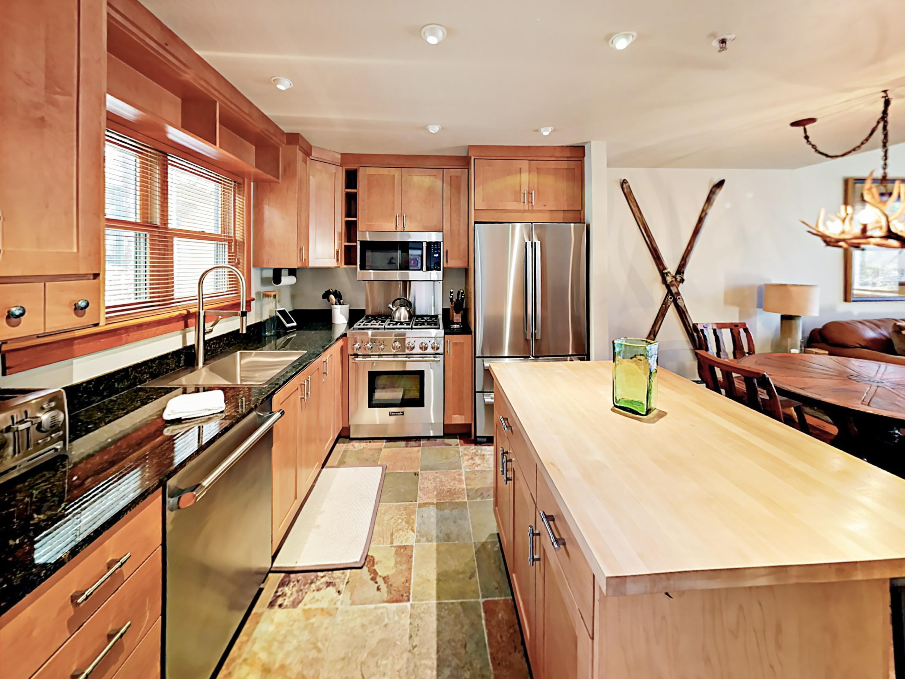 Stainless steel appliances include a gas range and a French door refrigerator.