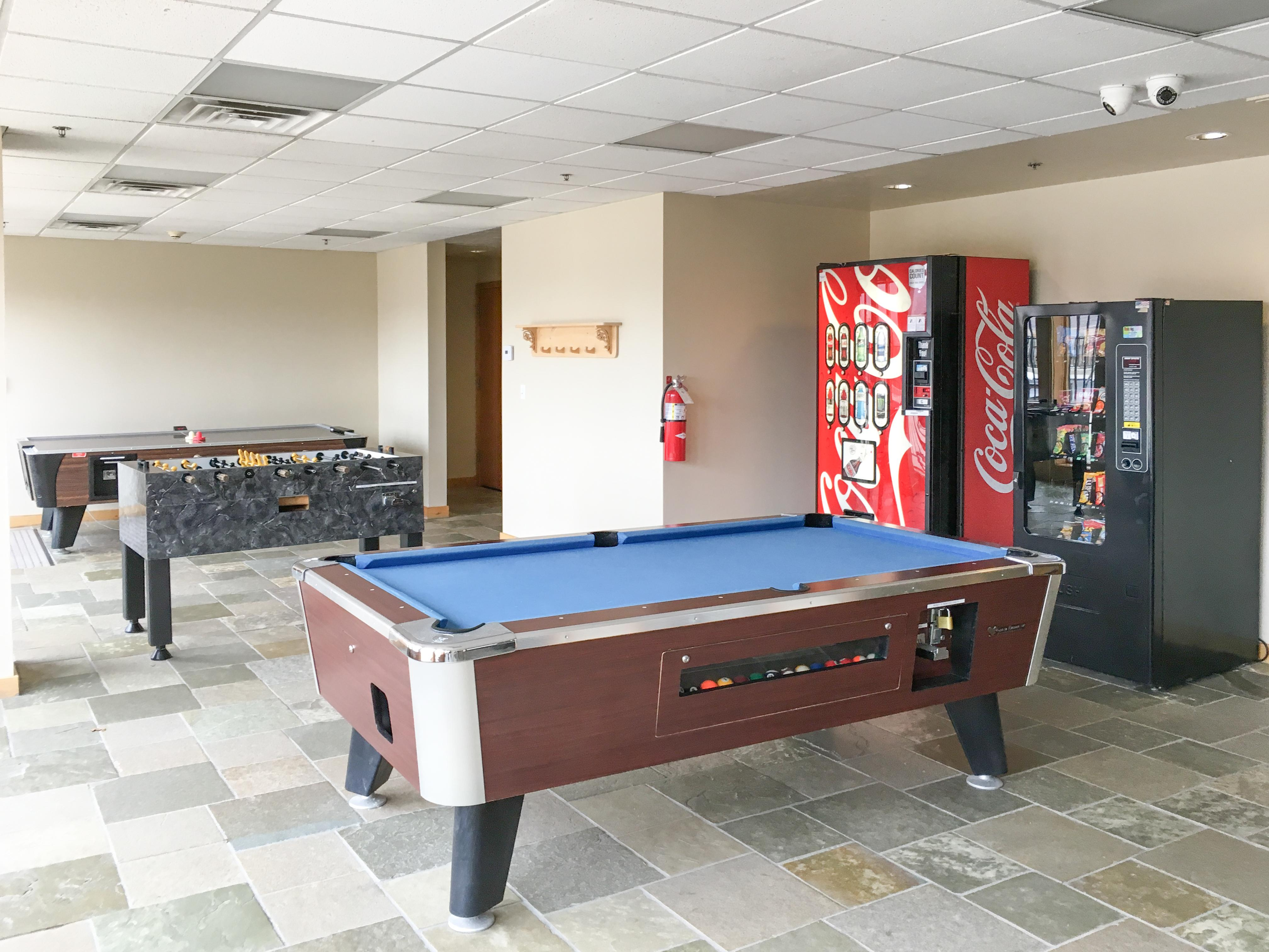 A fun game room includes several pool tables and a foosball table.