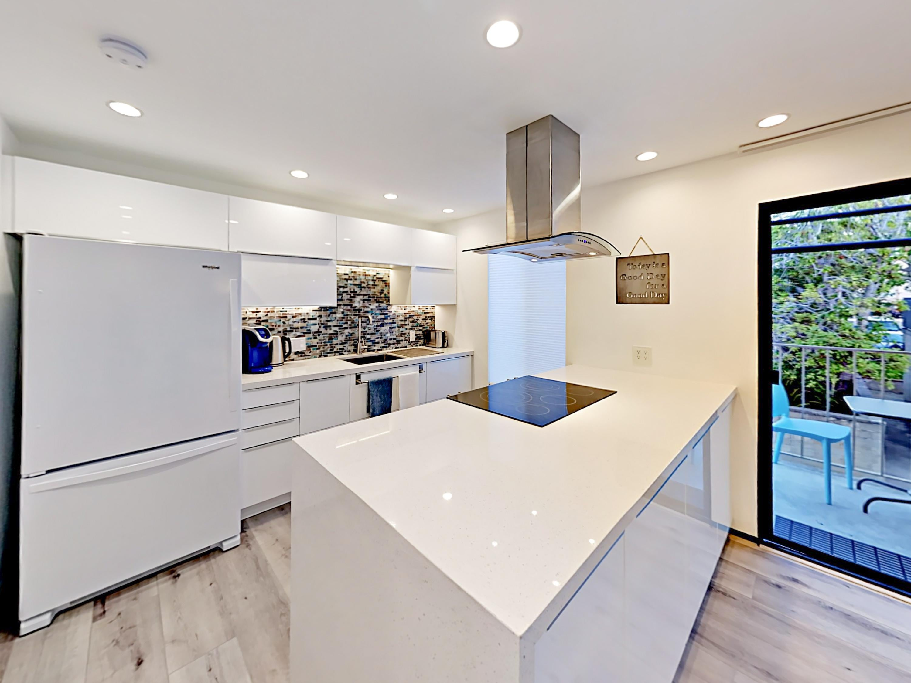 The Euro-style kitchen features sparkling quartz countertops and high-end appliances.