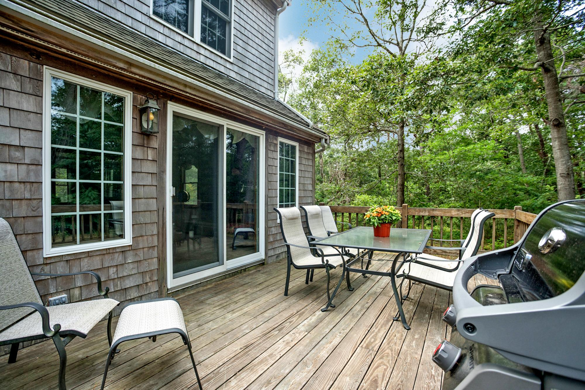 A large deck features alfresco dining and a grill.