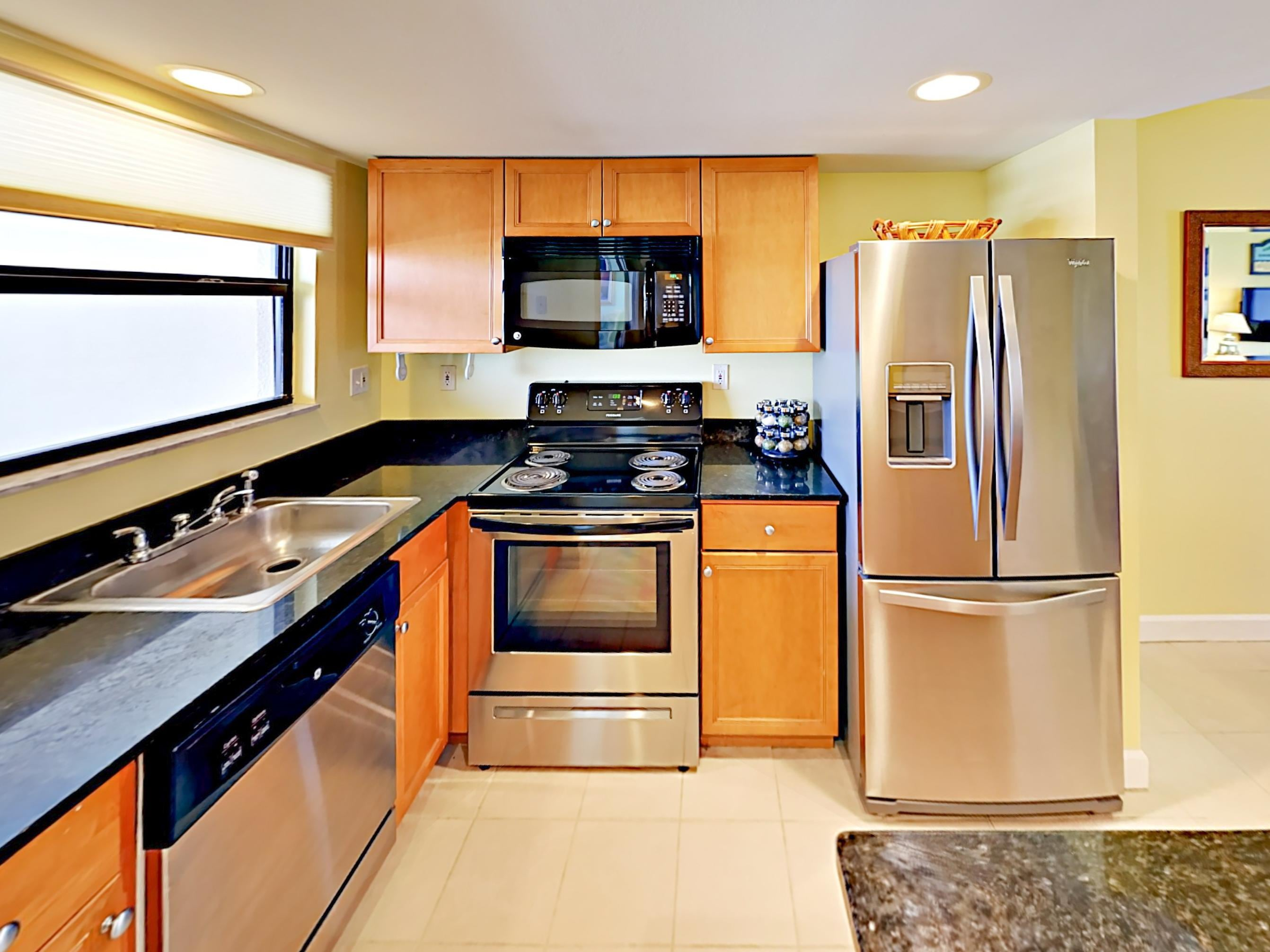 Granite countertops, stainless steel appliances, and rich wood cabinets await in the kitchen. TurnKey stocks a starter supply of dish soap and paper towels.