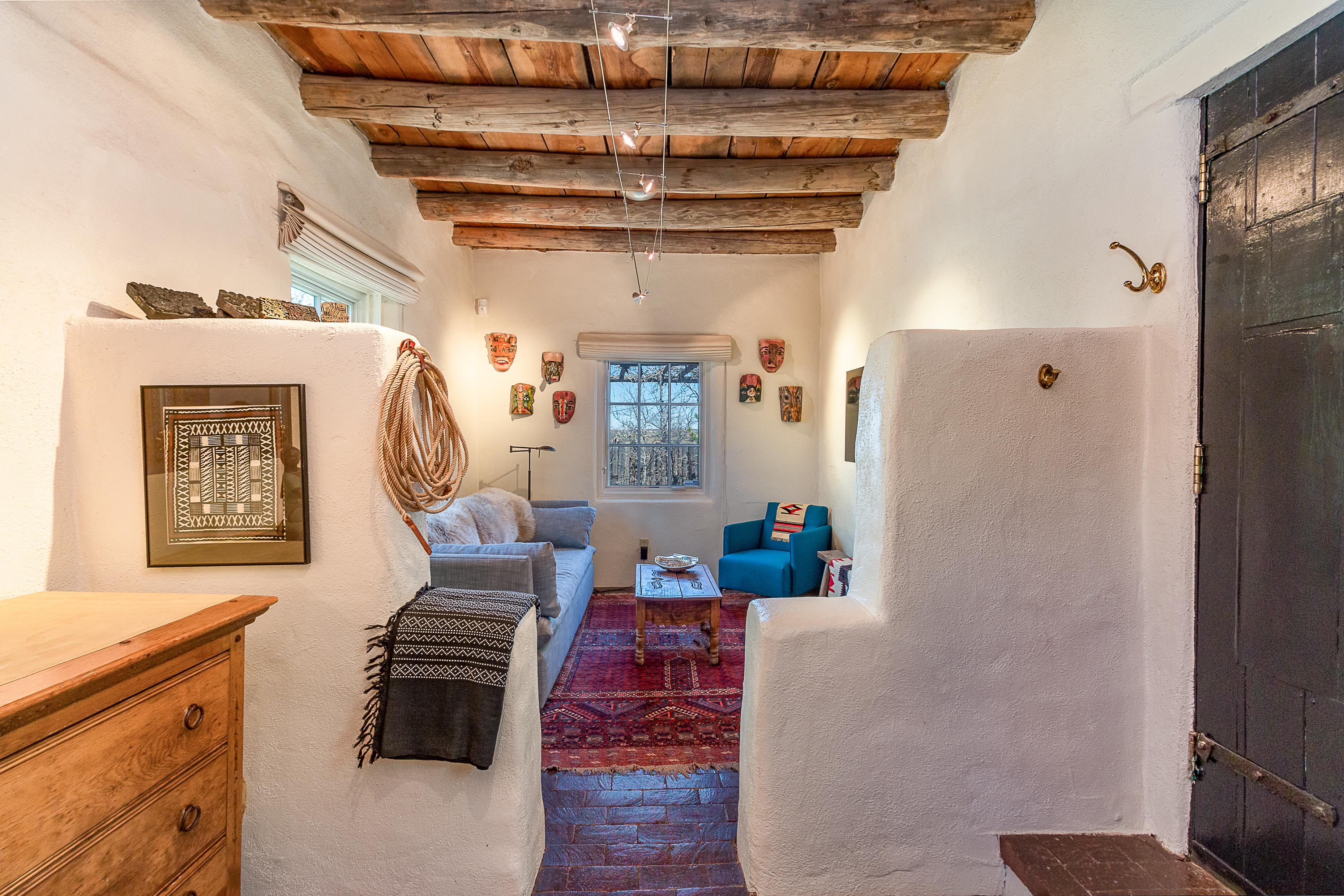 "The living area is situated behind a traditional ""key"" style adobe opening, and features ample seating and local crafts."