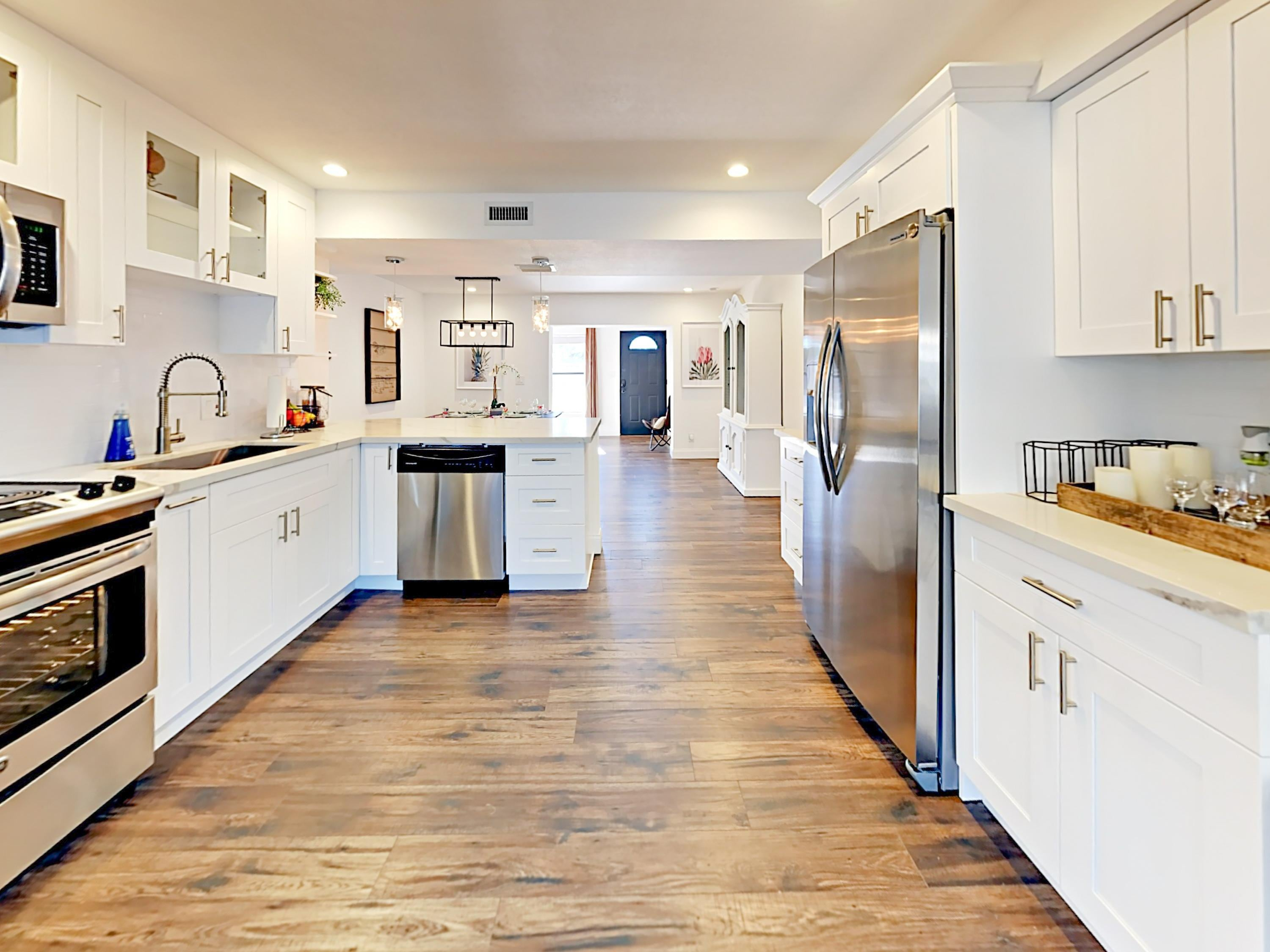 Welcome to Lantana! White marble countertops line a posh kitchen, outfitted with stainless steel appliances.