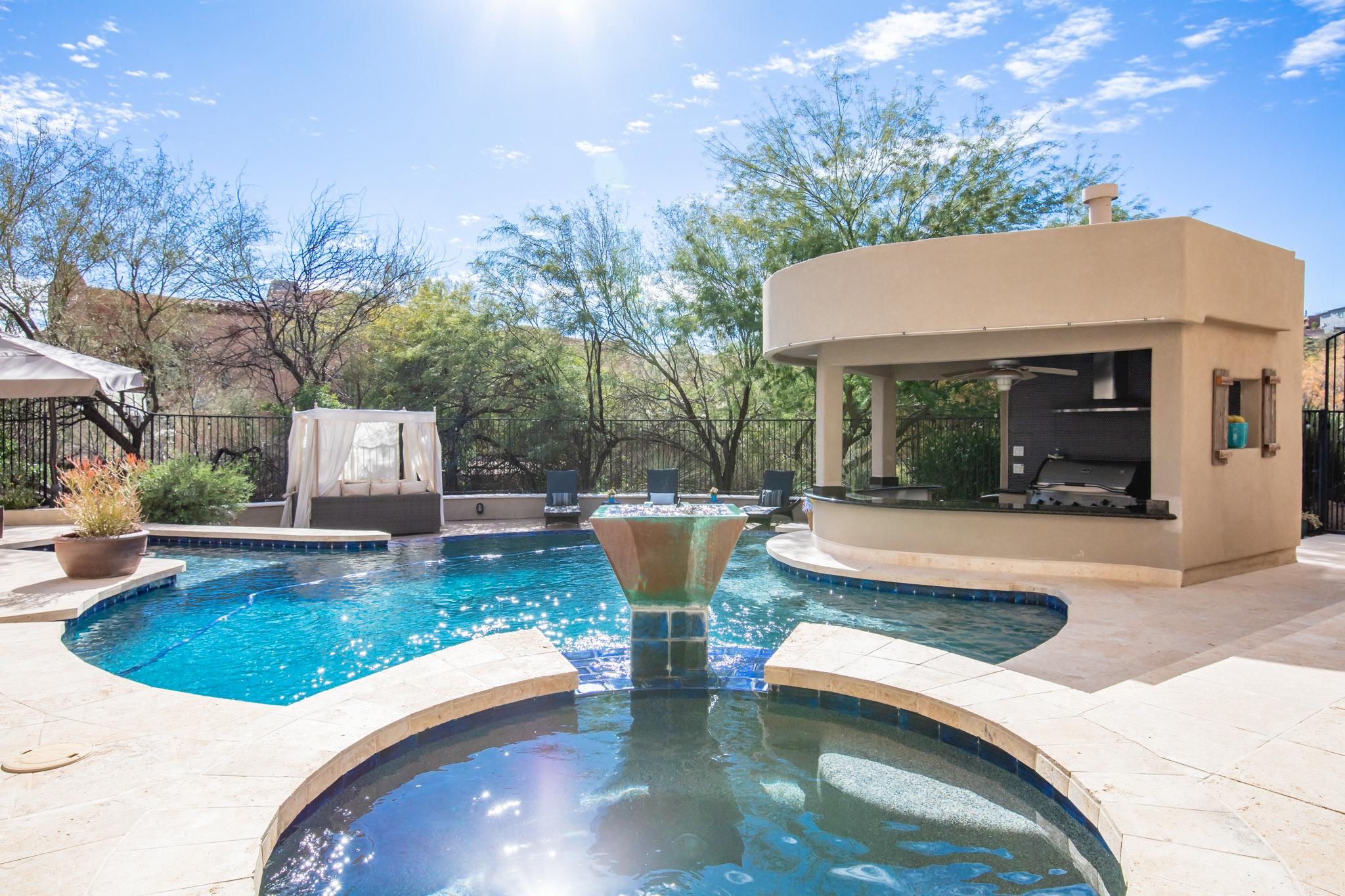 The unbelievable outdoor entertaining space features a heated pool, hot tub, cabana, and covered kitchen area.