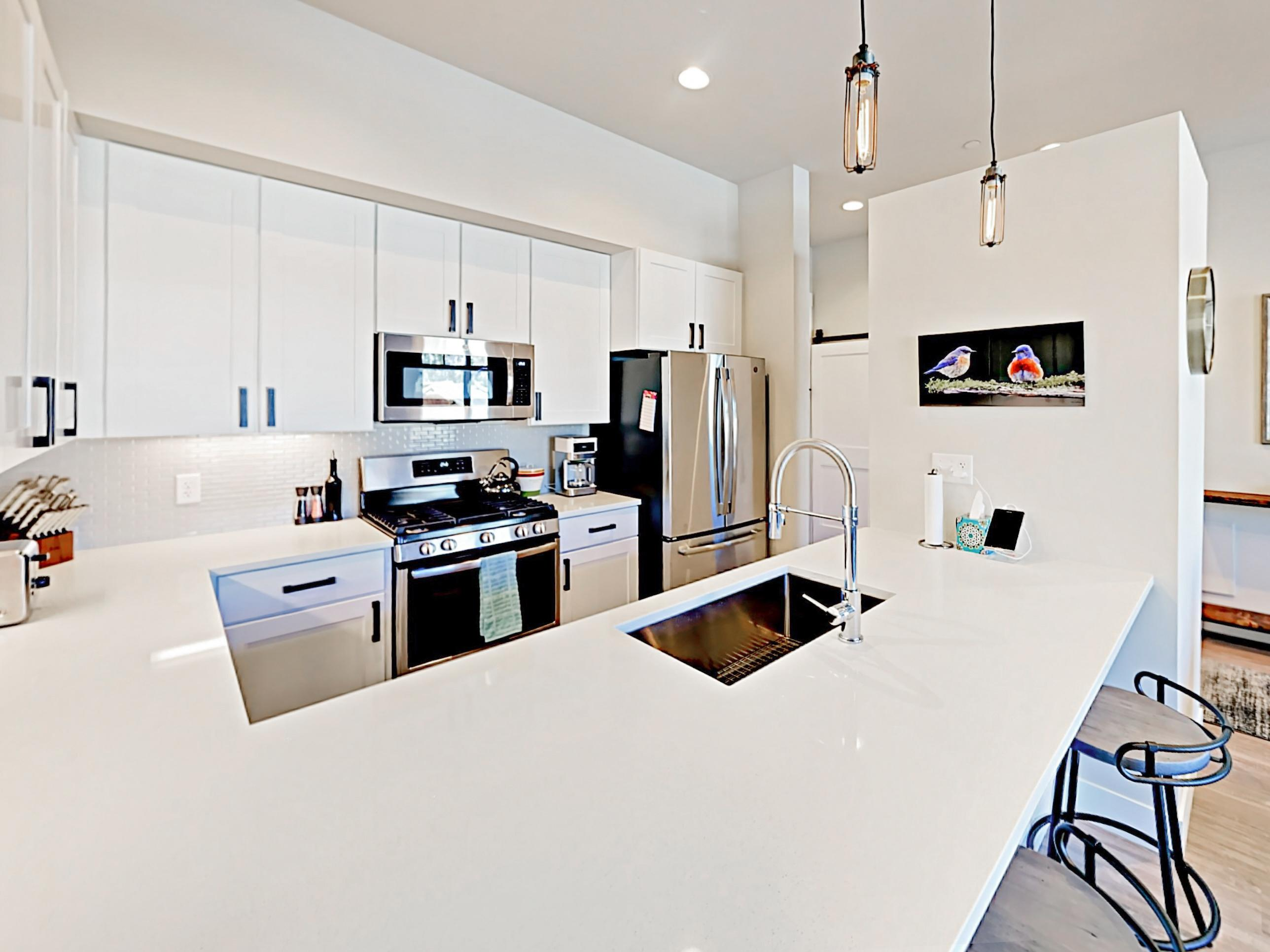Gleaming white quartz countertops offer plenty of prep space in the kitchen.
