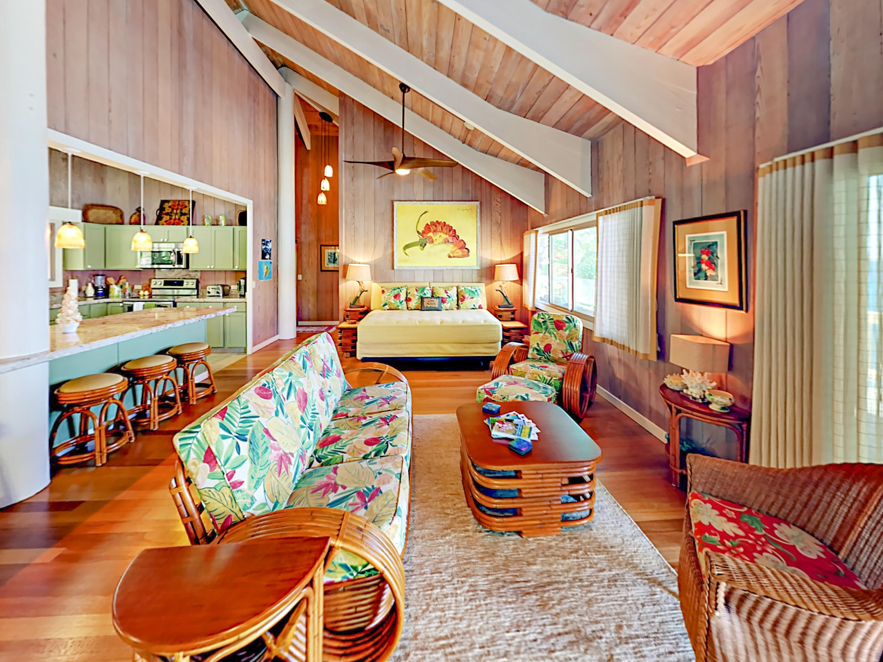 Hardwood floors, wood paneling, and vaulted ceilings give the modern living area a touch of traditional Hawaiian charm.