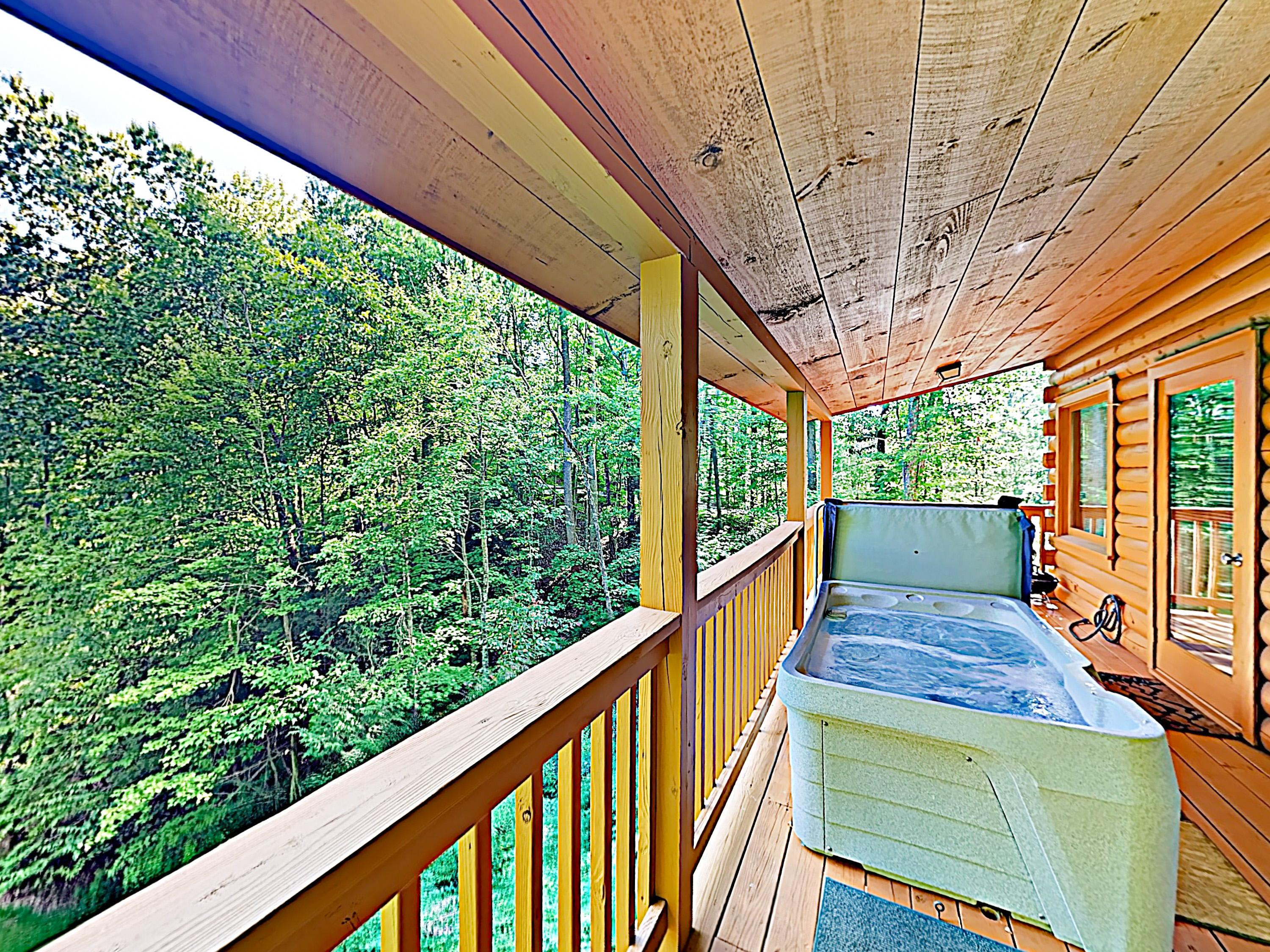 The covered deck includes a private hot tub.