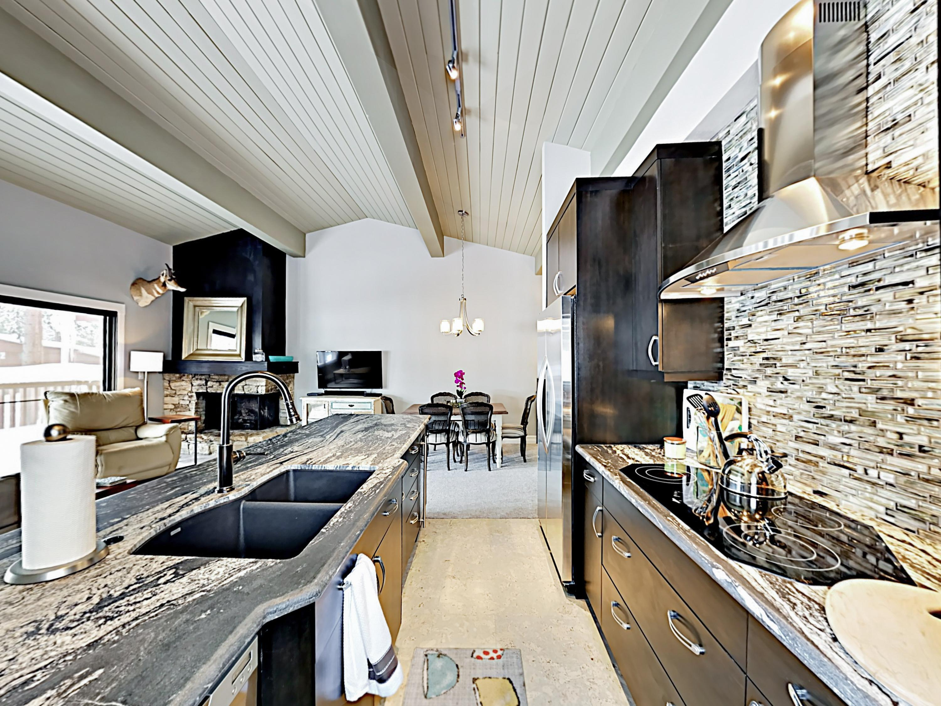 The modern kitchen is outfitted with a full suite of stainless steel appliances, a stylish tile backsplash, and granite countertops.