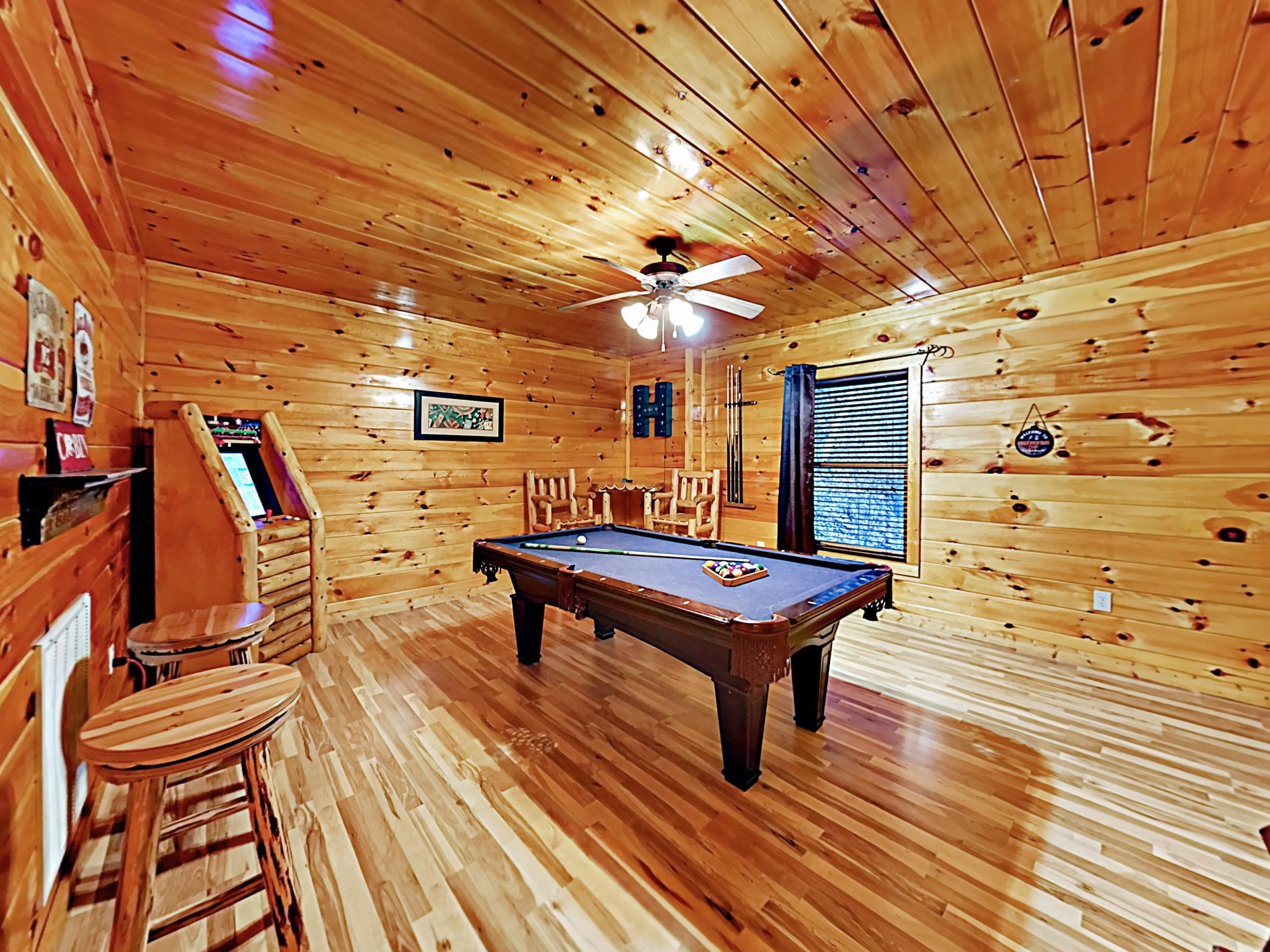 The game room features a pool table, arcade system, and flat-screen TV (not pictured).