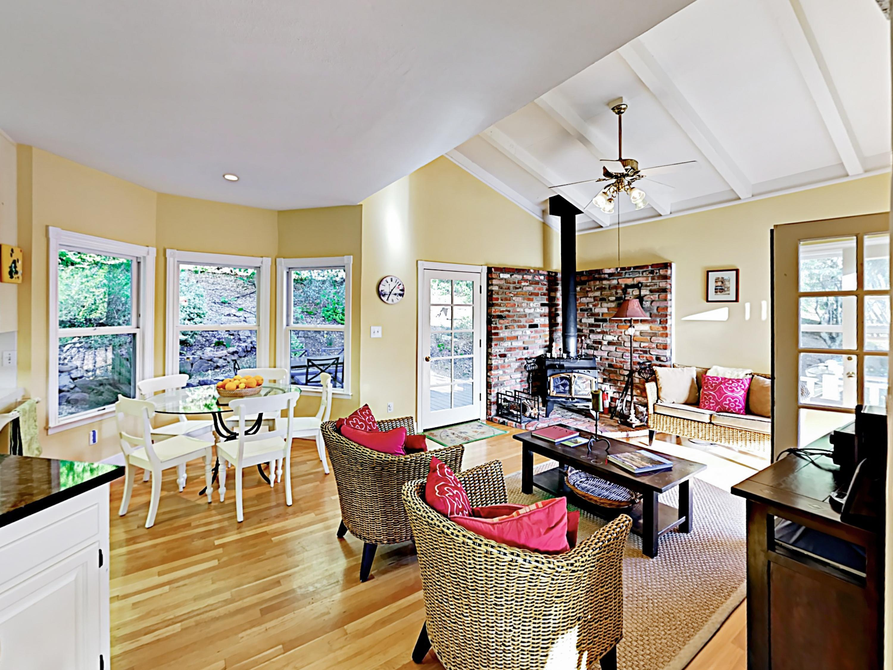 A light-filled and open breakfast nook features comfy wicker seating and a wood-burning stove.