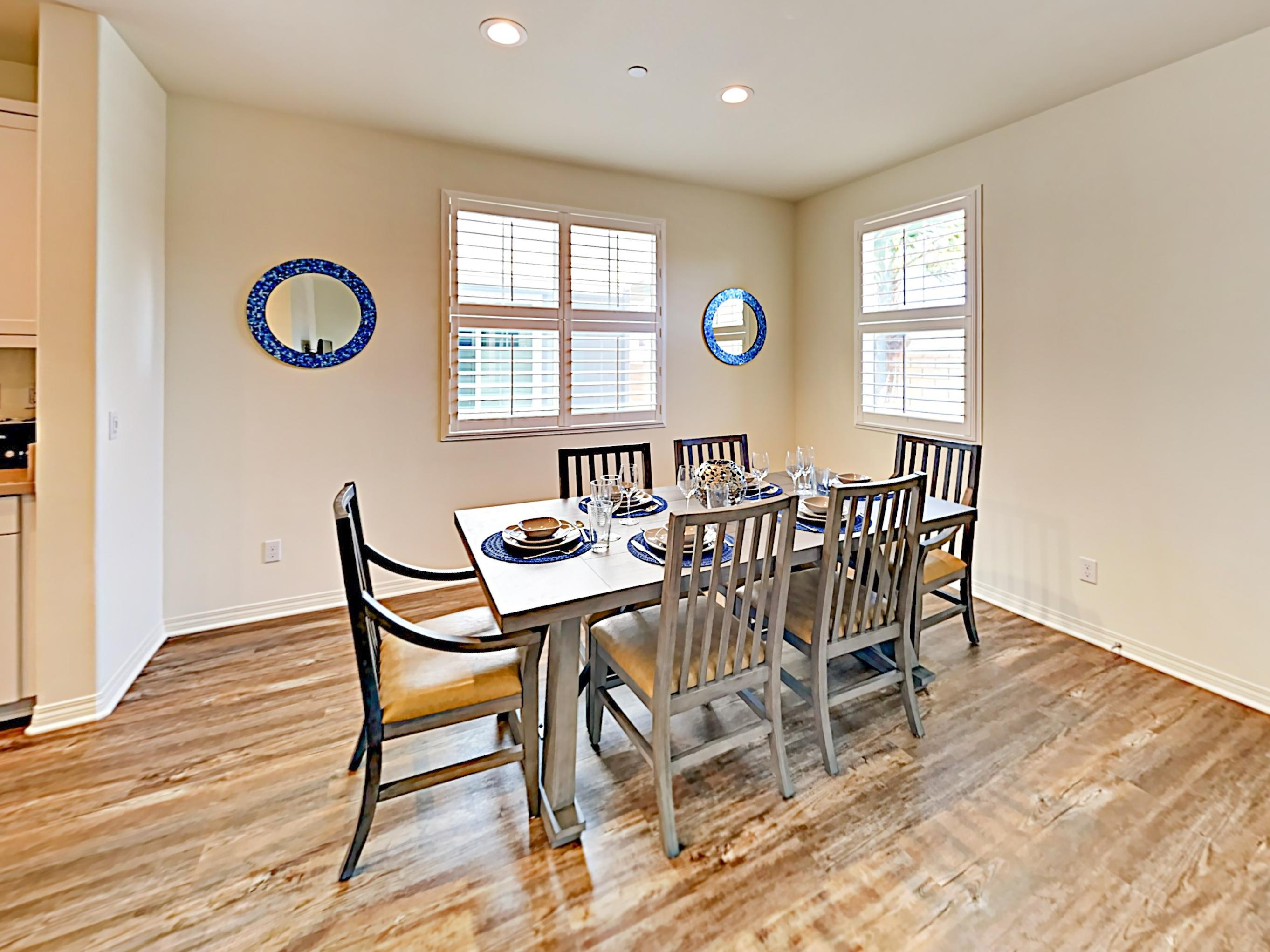 A wooden dining table offers comfortable seating for 6.
