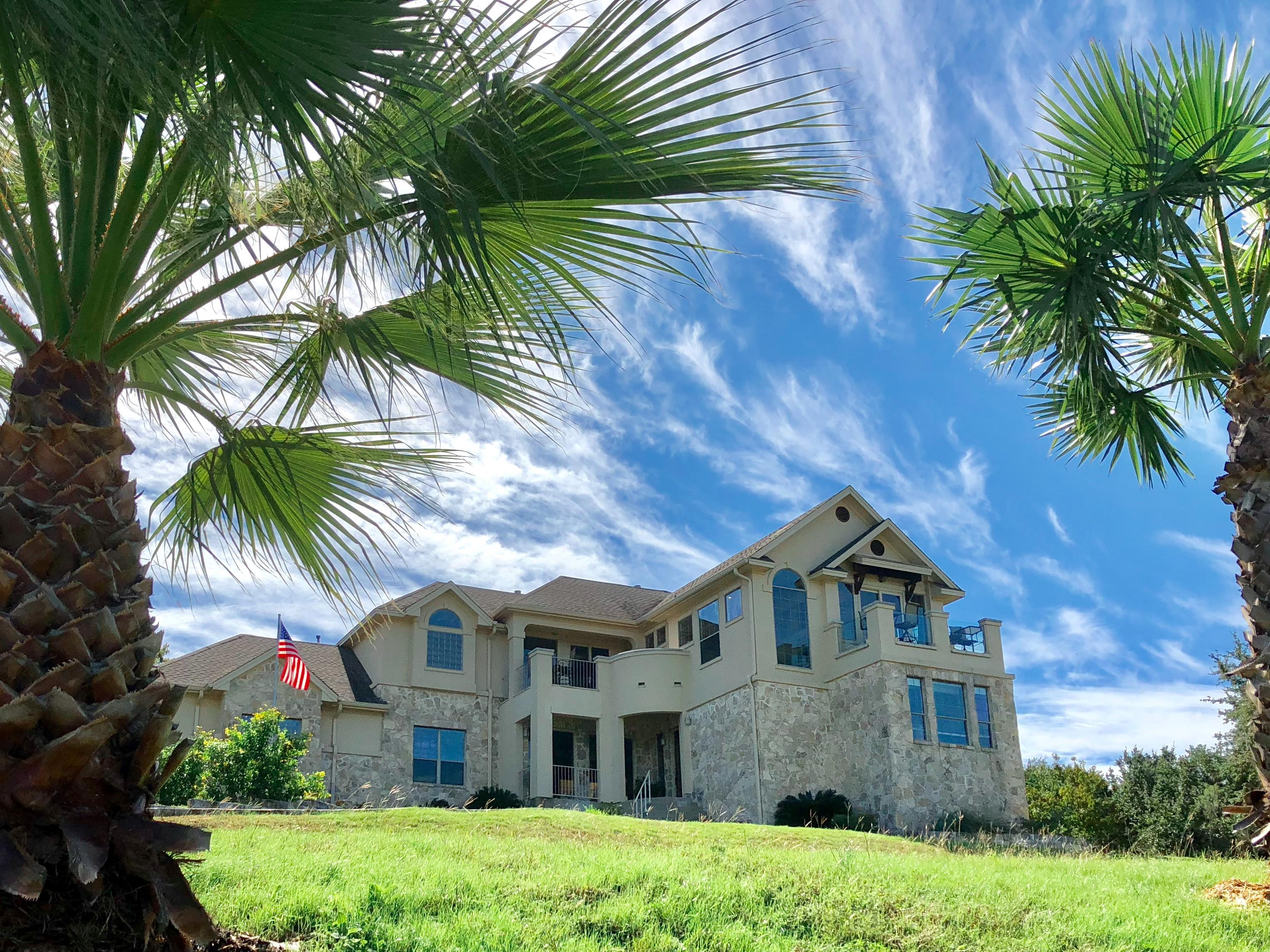 Welcome! This stunning home is professionally managed by TurnKey Vacation Rentals.This stunning estate is bordered by beautiful landscape including mature palm trees.