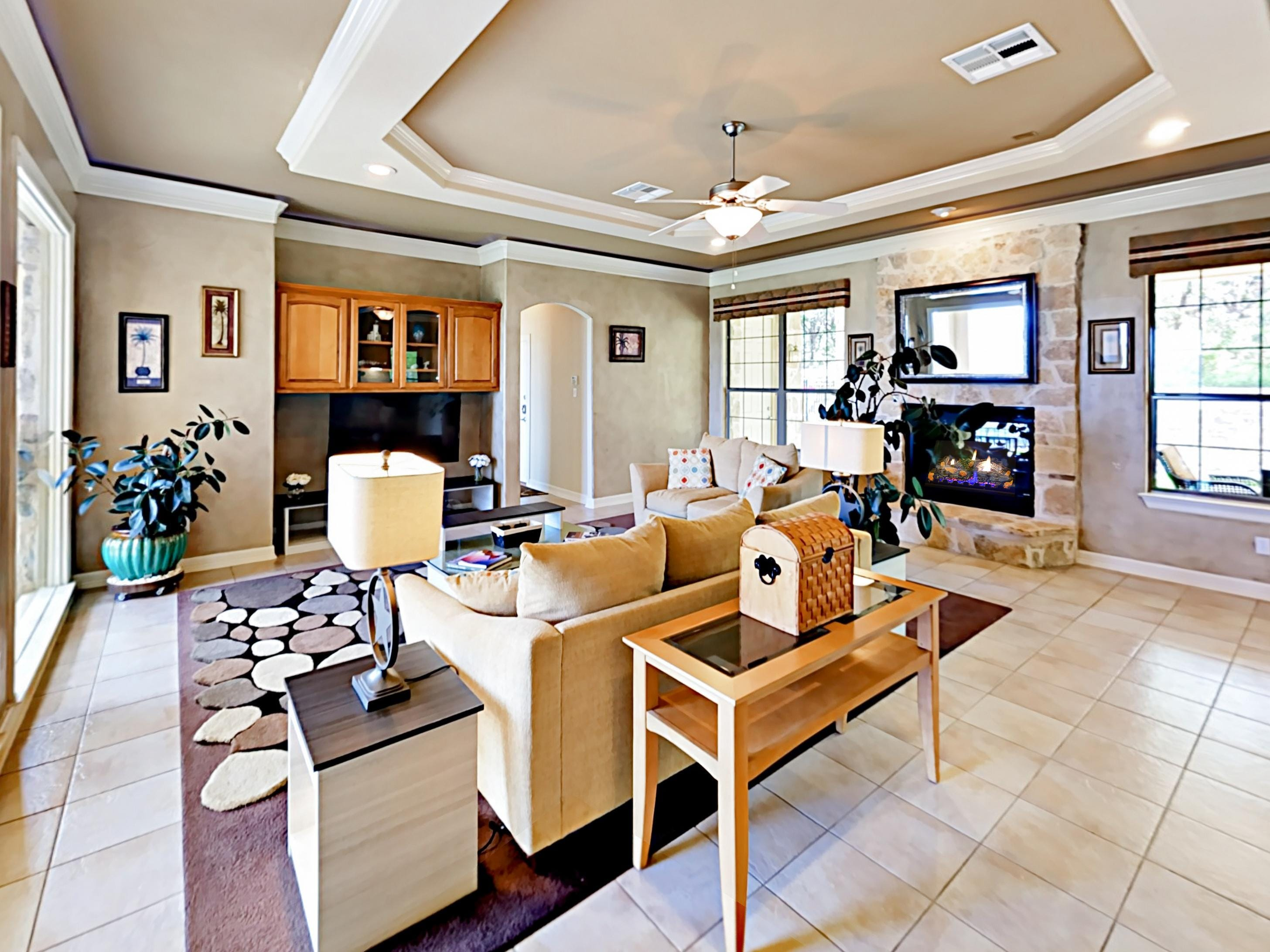 "Find comfort in the lavish living area, furnished with a matching sofa and love seat, a fireplace, and a 55"" cable TV."