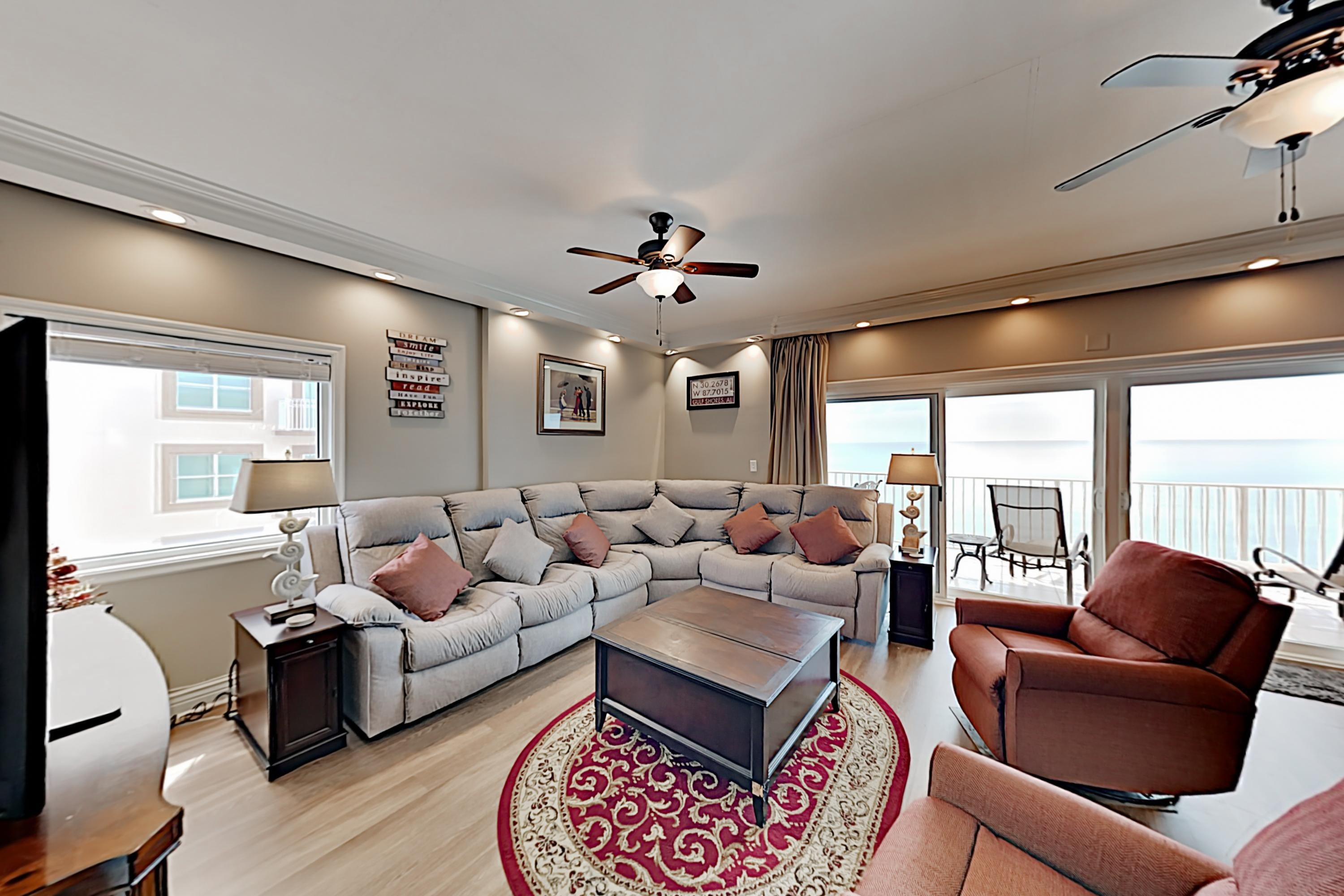 A light-filled living area features a large sectional and 2 plush armchairs.