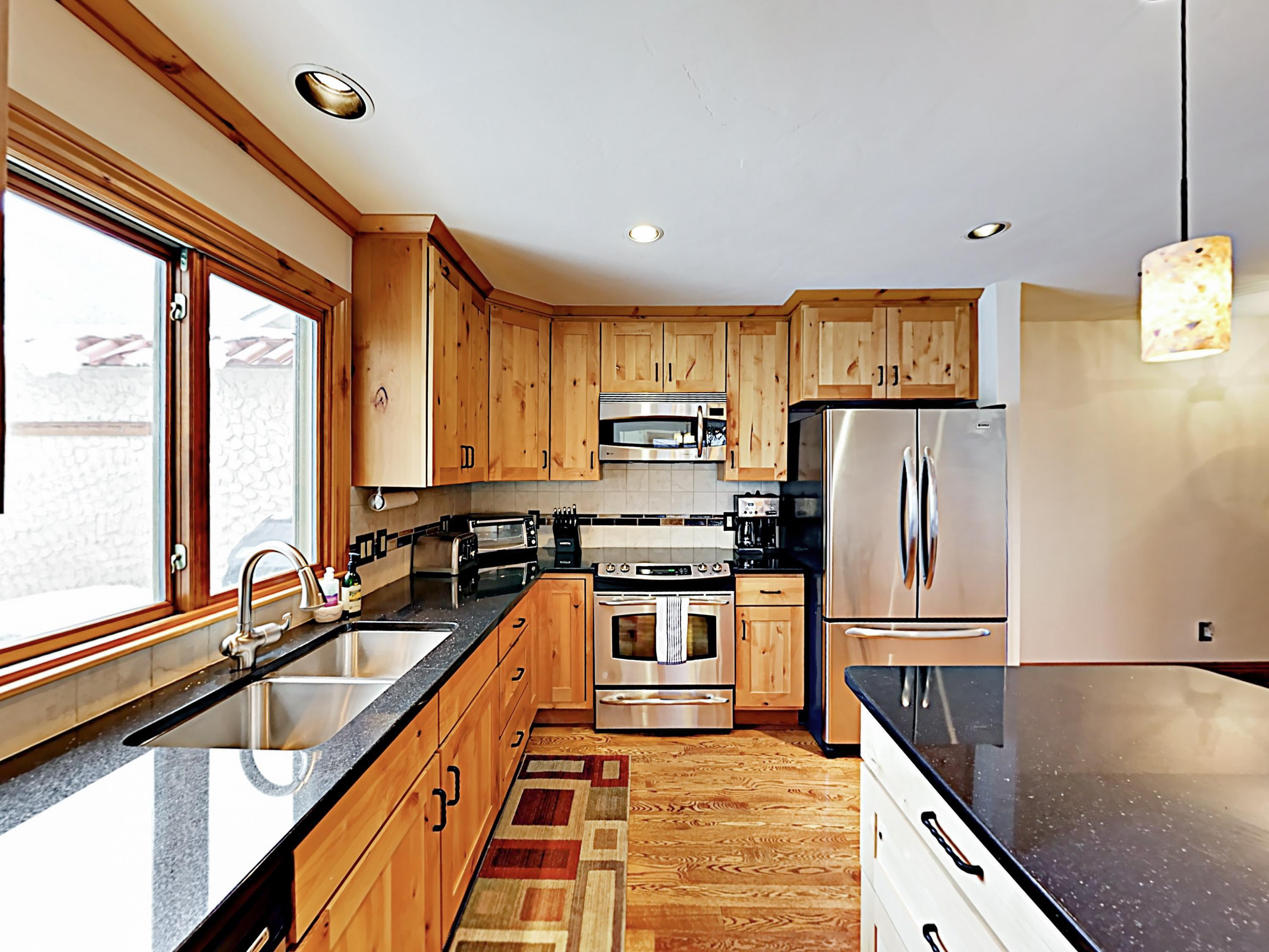 A well-equipped kitchen is outfitted with stainless steel appliances, including a  roomy French door refrigerator.