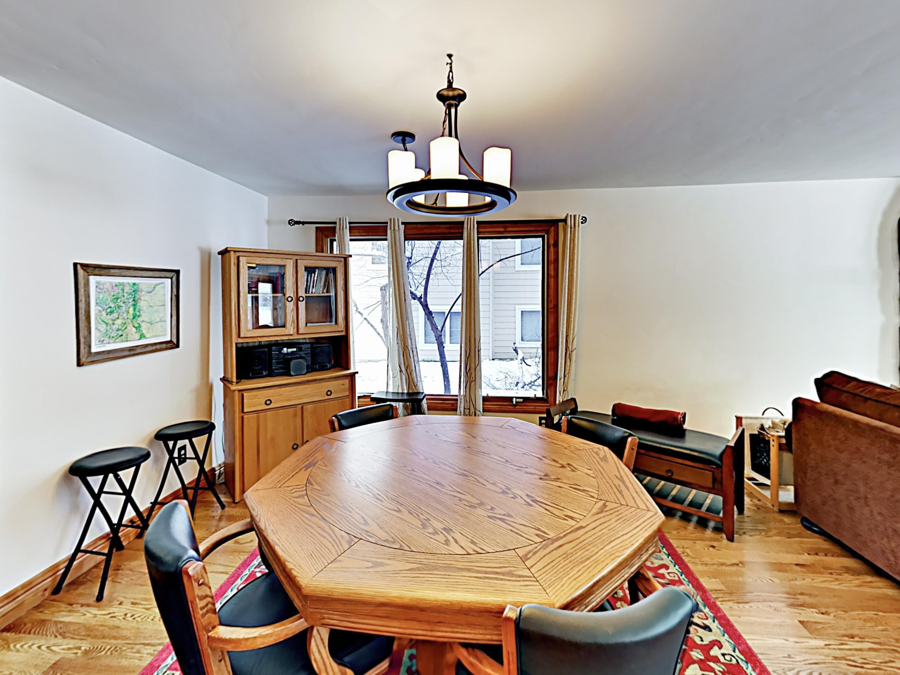 A wooden dining table offers comfy seating for 4.