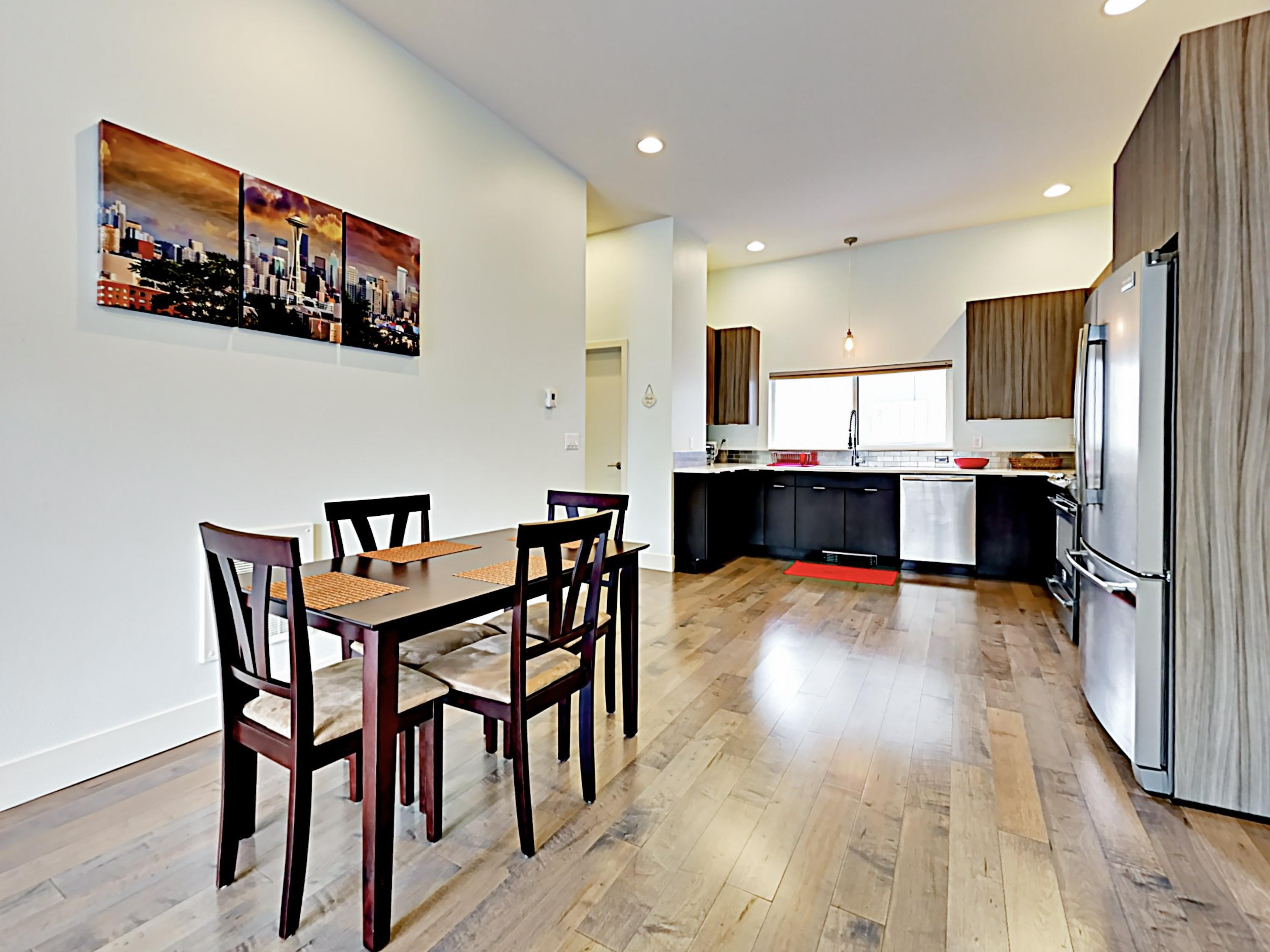 The spacious and open kitchen/dining area boasts tall ceilings, sleek wooden flooring, and all-new furnishings.