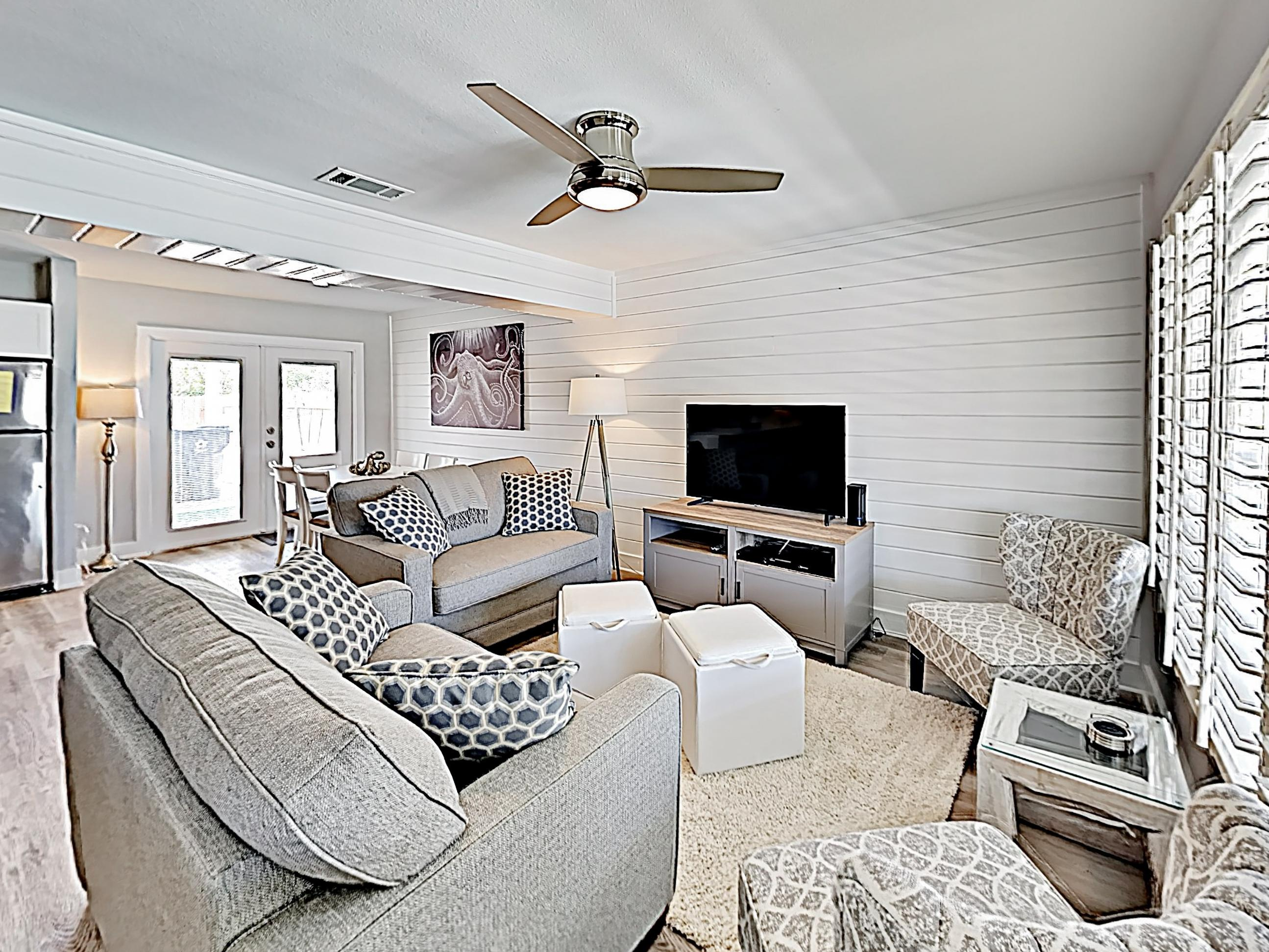 The modern living room is detailed with a cool grey palette and shiplap walls.