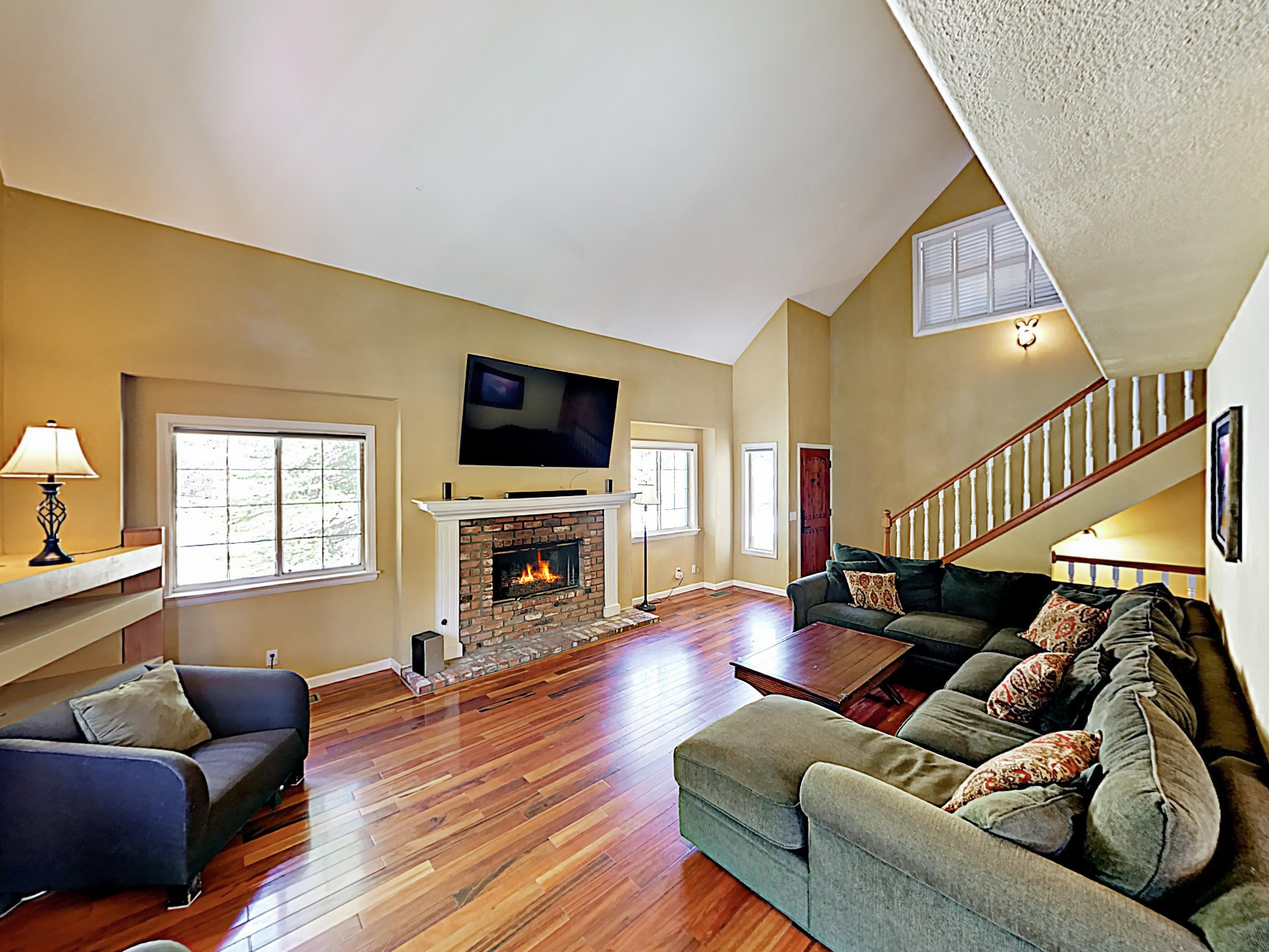 "A wood-burning fireplace and 75"" TV await in the main living area."