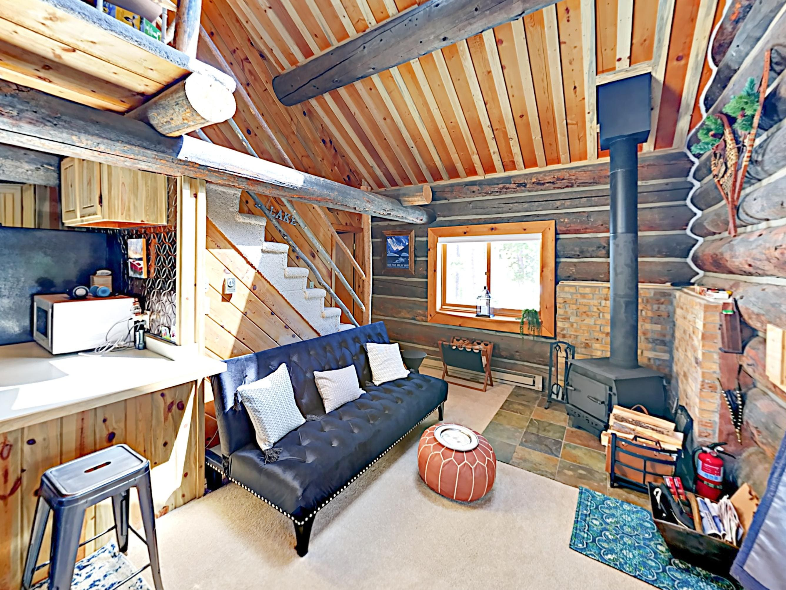 The inviting living are has a wood-burning fireplace and a futon.
