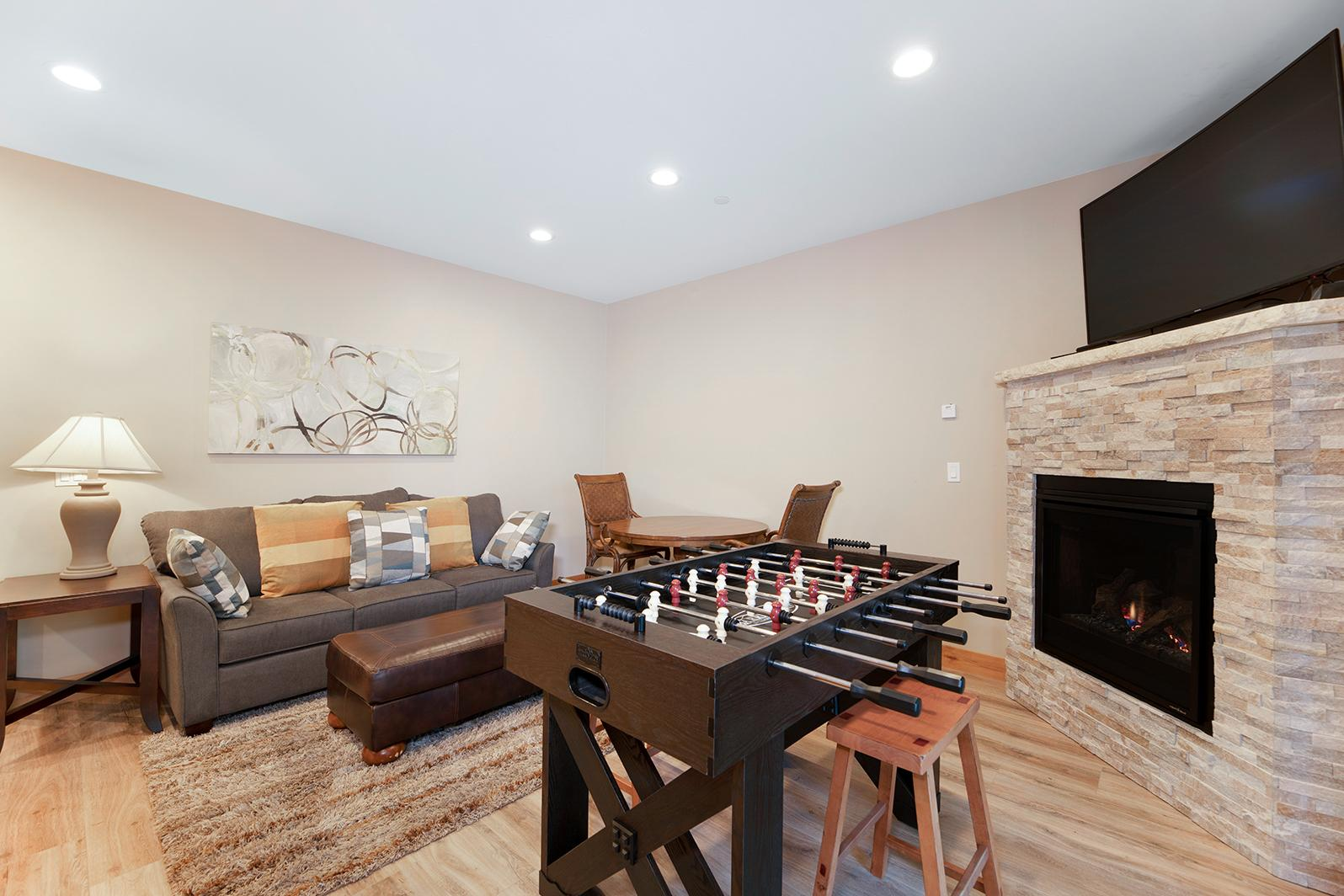 "The downstairs game room offers a foosball table, 55"" TV, and gas fireplace."
