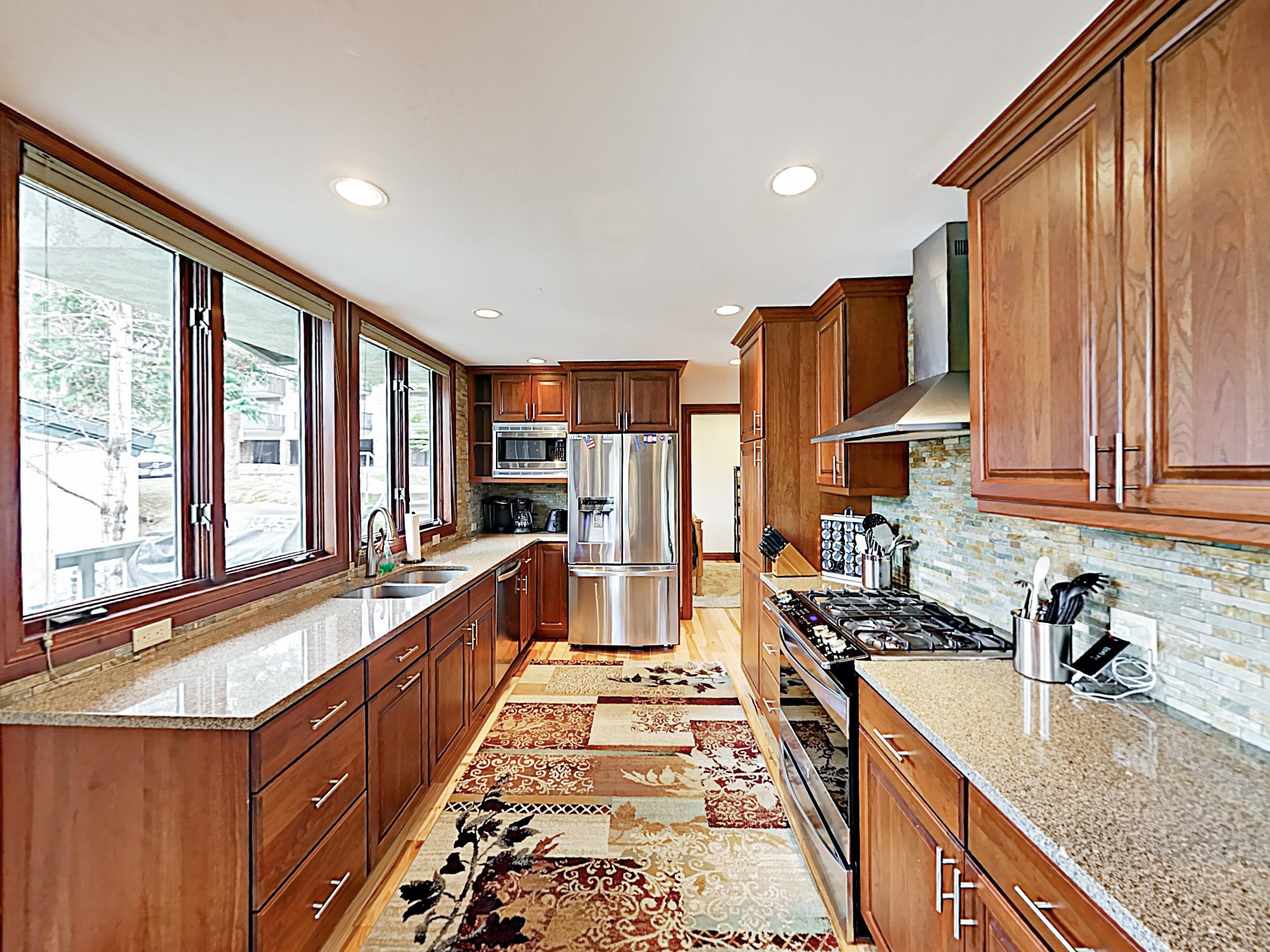 The gourmet kitchen features glossy granite countertops and a full suite of stainless steel appliances.