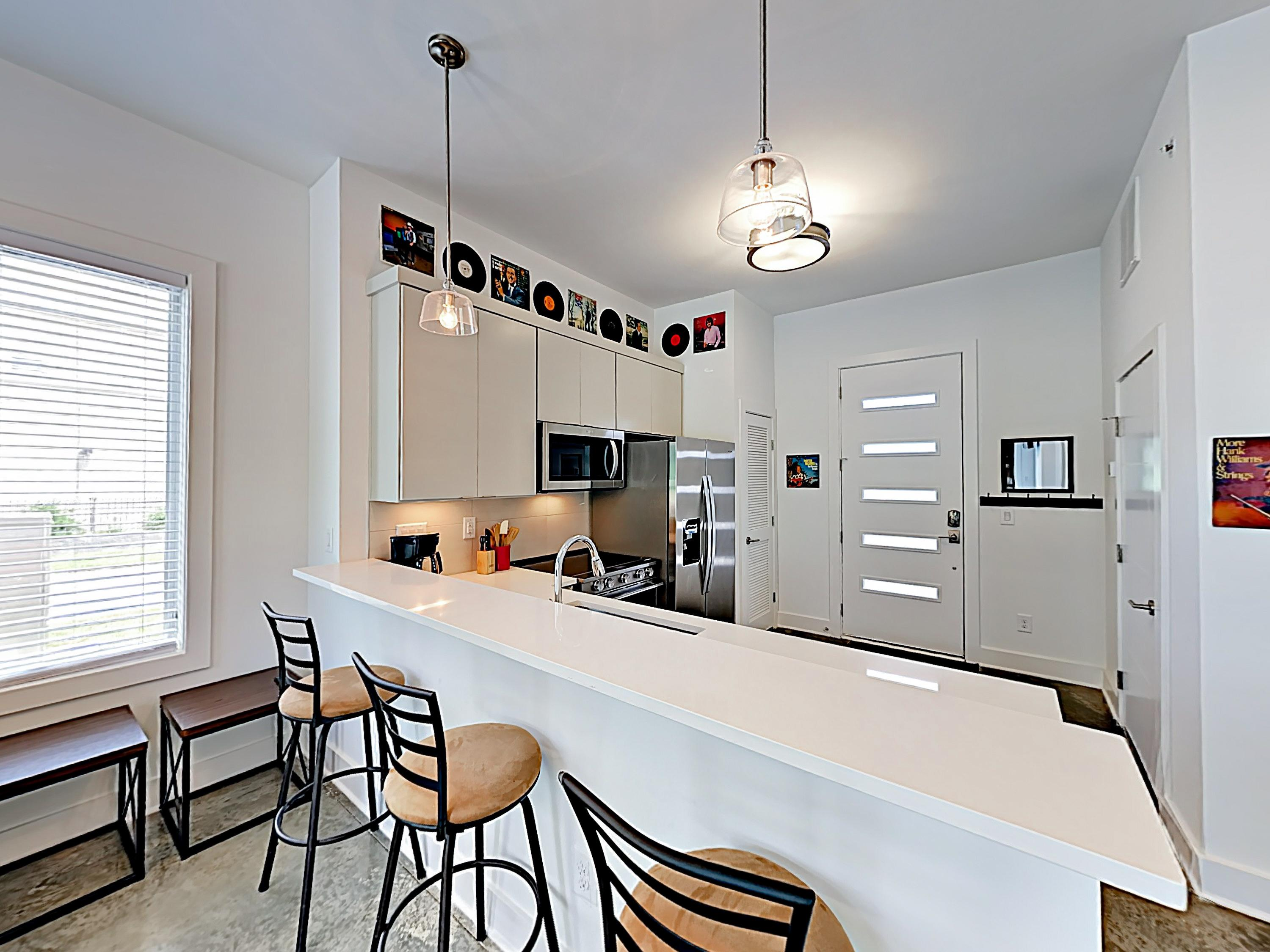 The modern, well-equipped kitchen has a breakfast bar with seating for 3.
