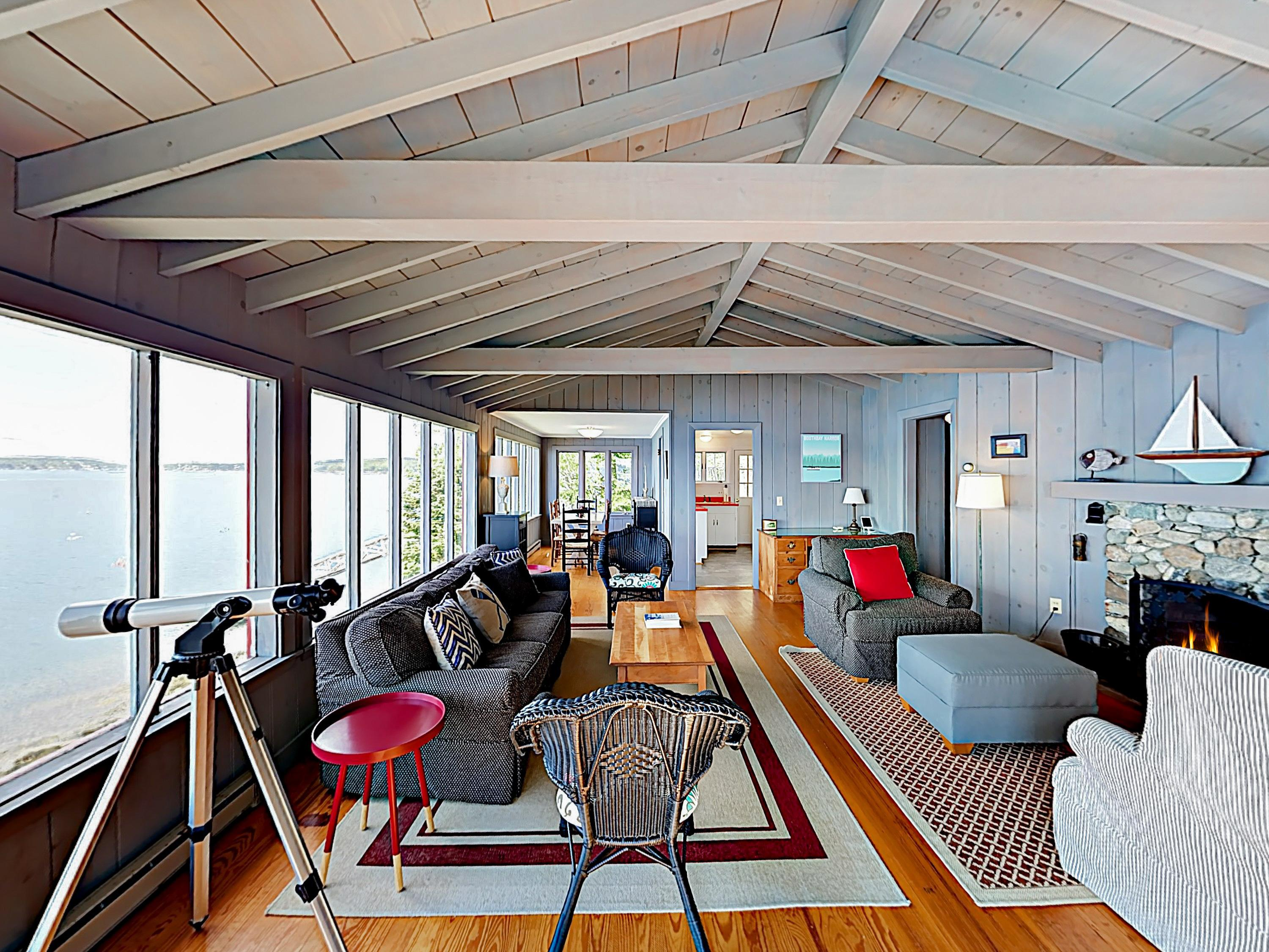In the main cottage, an open-concept living area offers ample natural light and panoramic bay views.