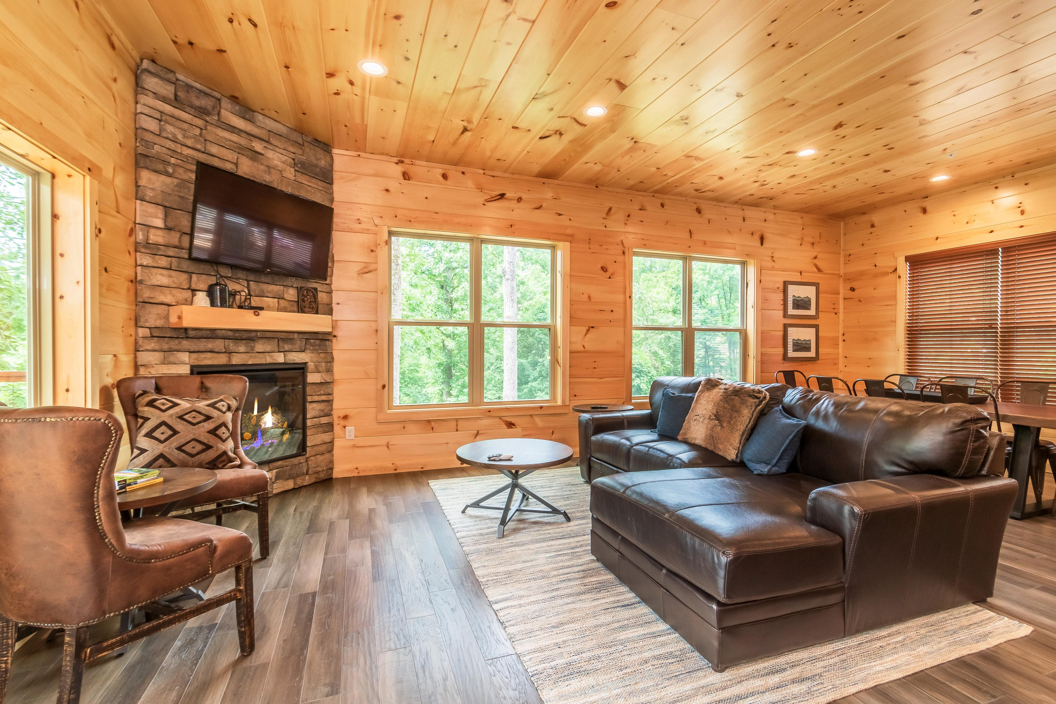 "Warm wood flows from floor to ceiling in the living room, detailed with a 52"" TV and a fireplace."