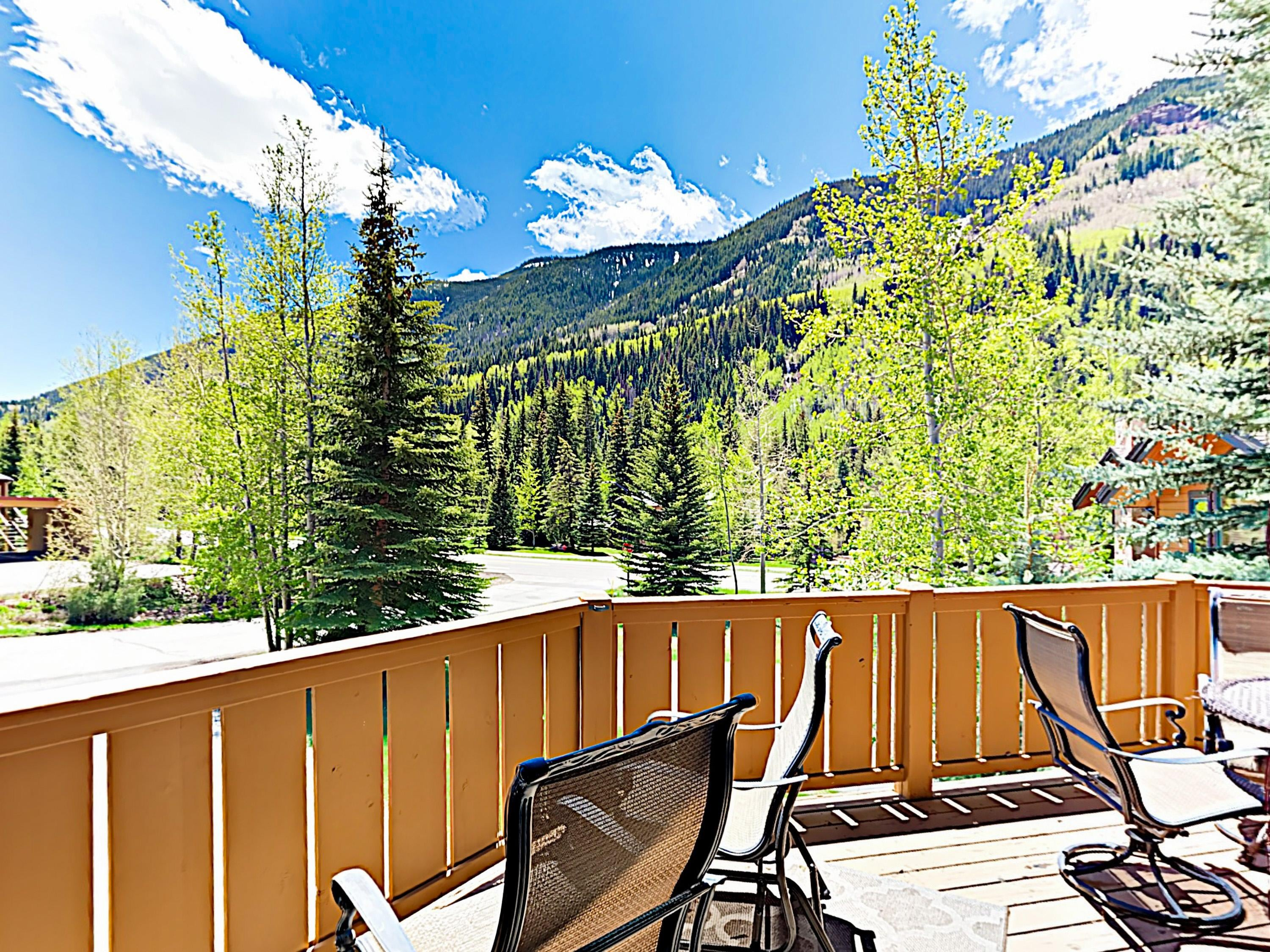 Unwind on a private deck, set before a backdrop of tree-dotted mountains.