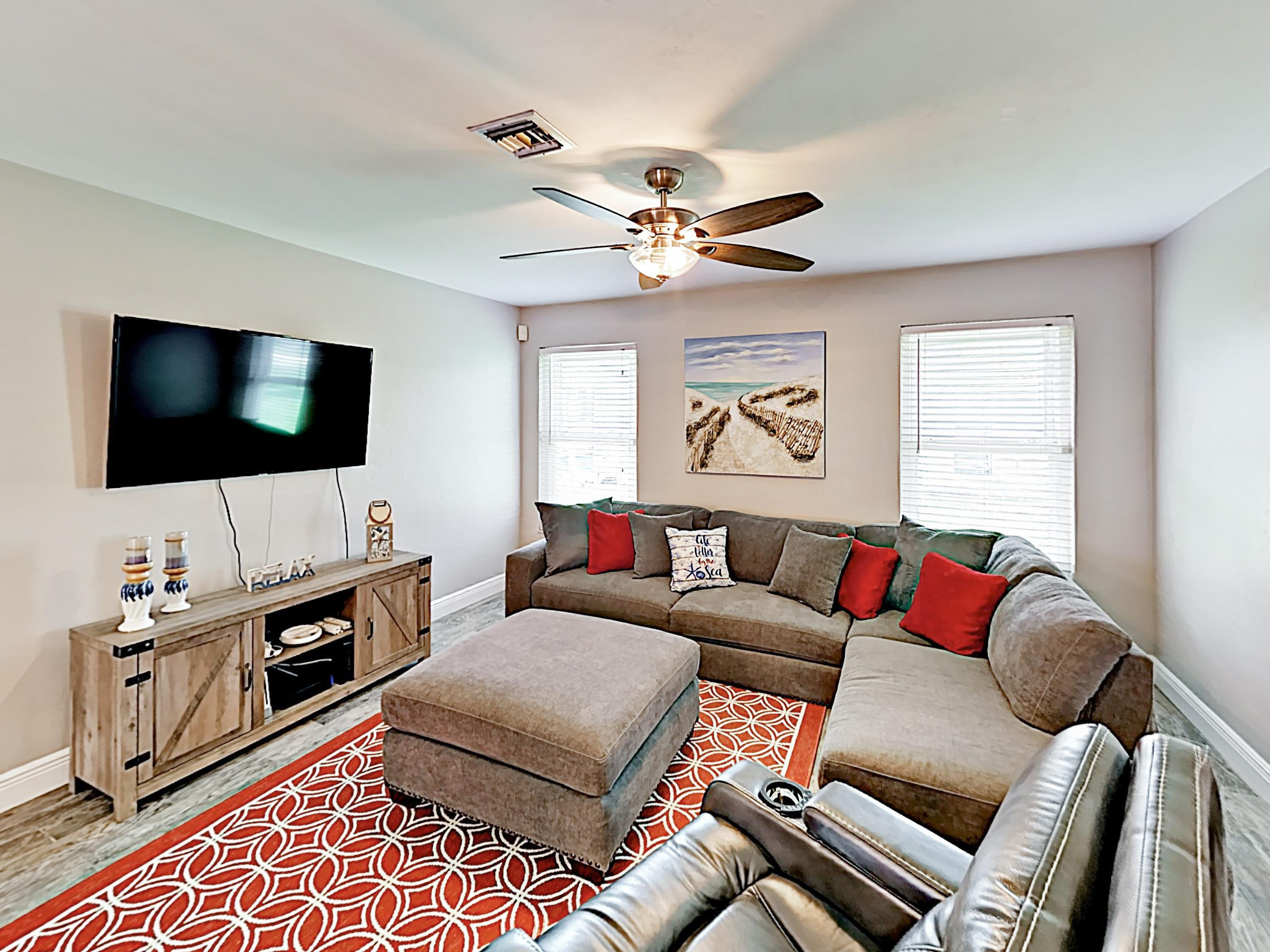 "Unwind in the living room, furnished with a plush sectional sofa, a recliner, and a 55"" flat-screen TV."